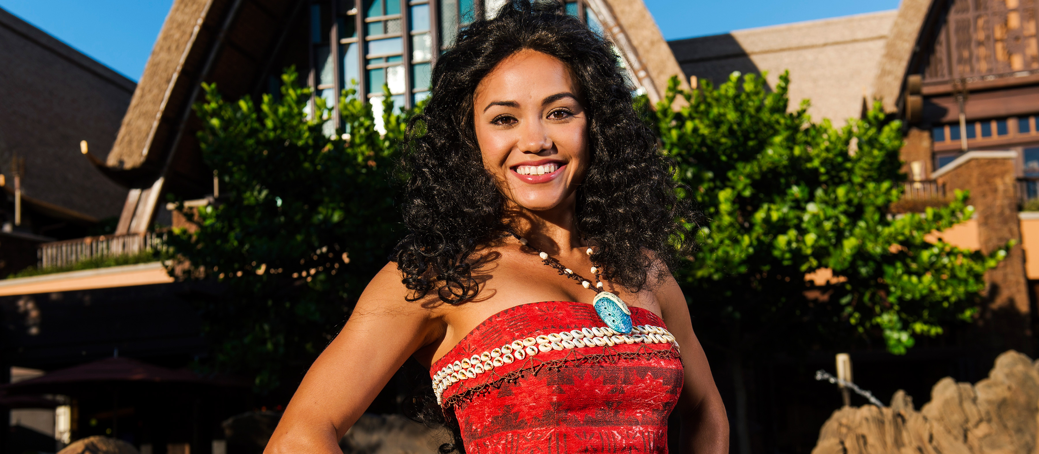 The Moana Character stands smiling in front of Aulani, wearing a top emblazoned with traditional island patterns and small seashells. Her signature necklace, with seashell charm, hangs around her neck.