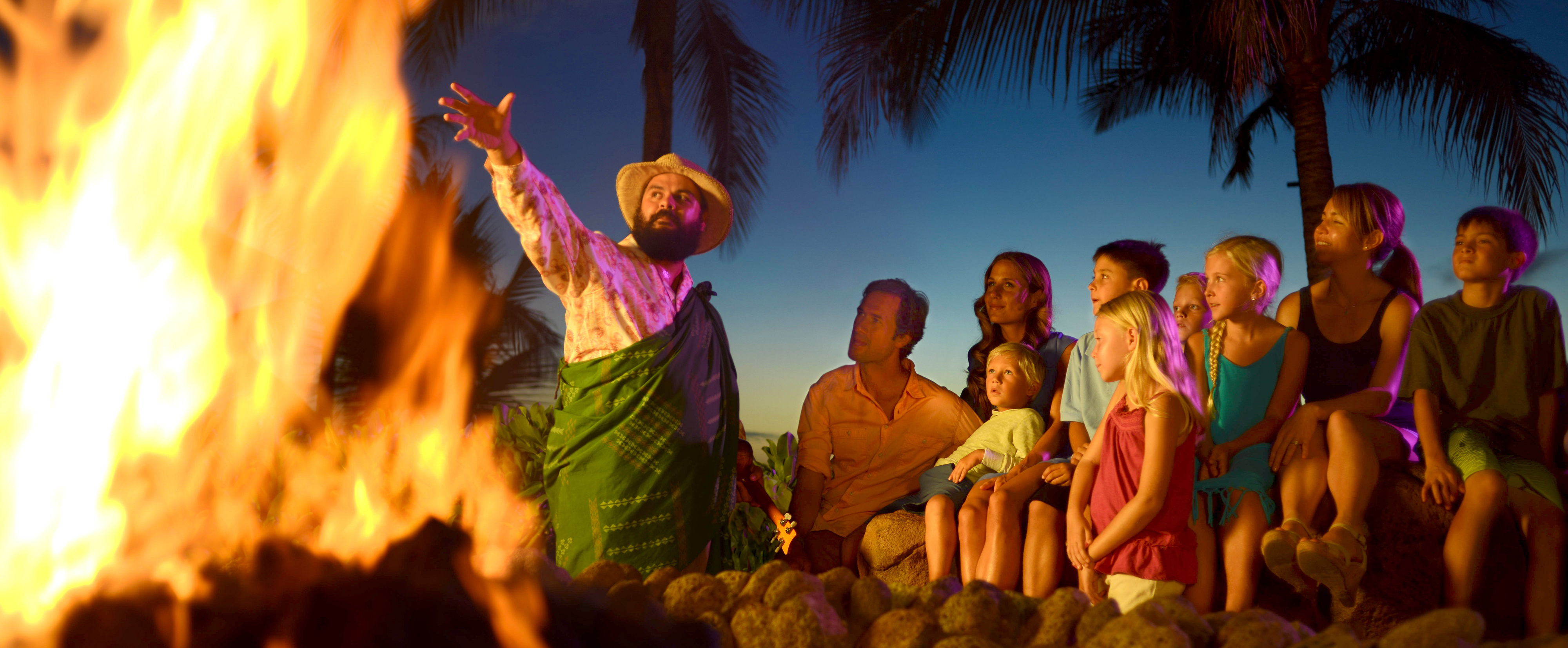 A man in a hat and sarong gestures dramatically toward a blazing fire pit while kids and parents watch