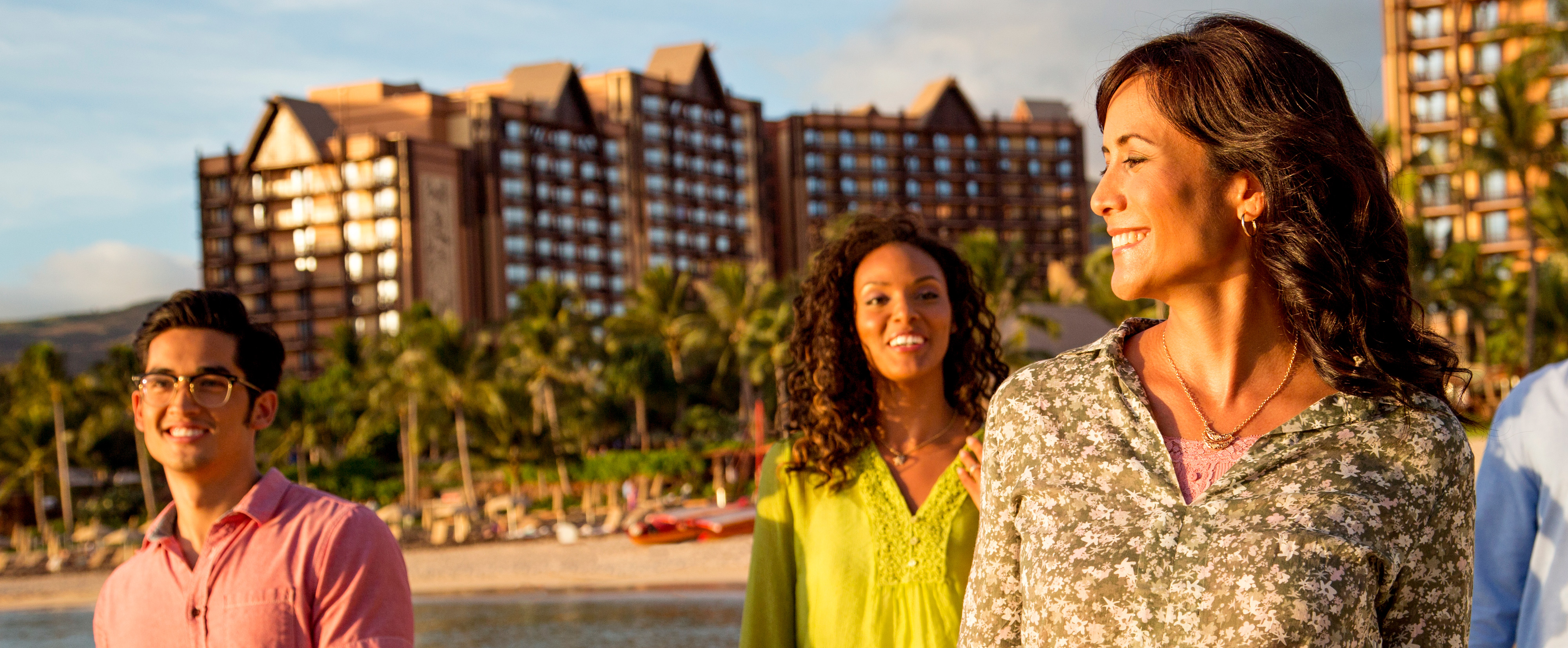 アウラニ・リゾート前のビーチを歩く若い男性と 2 人の若い女性。