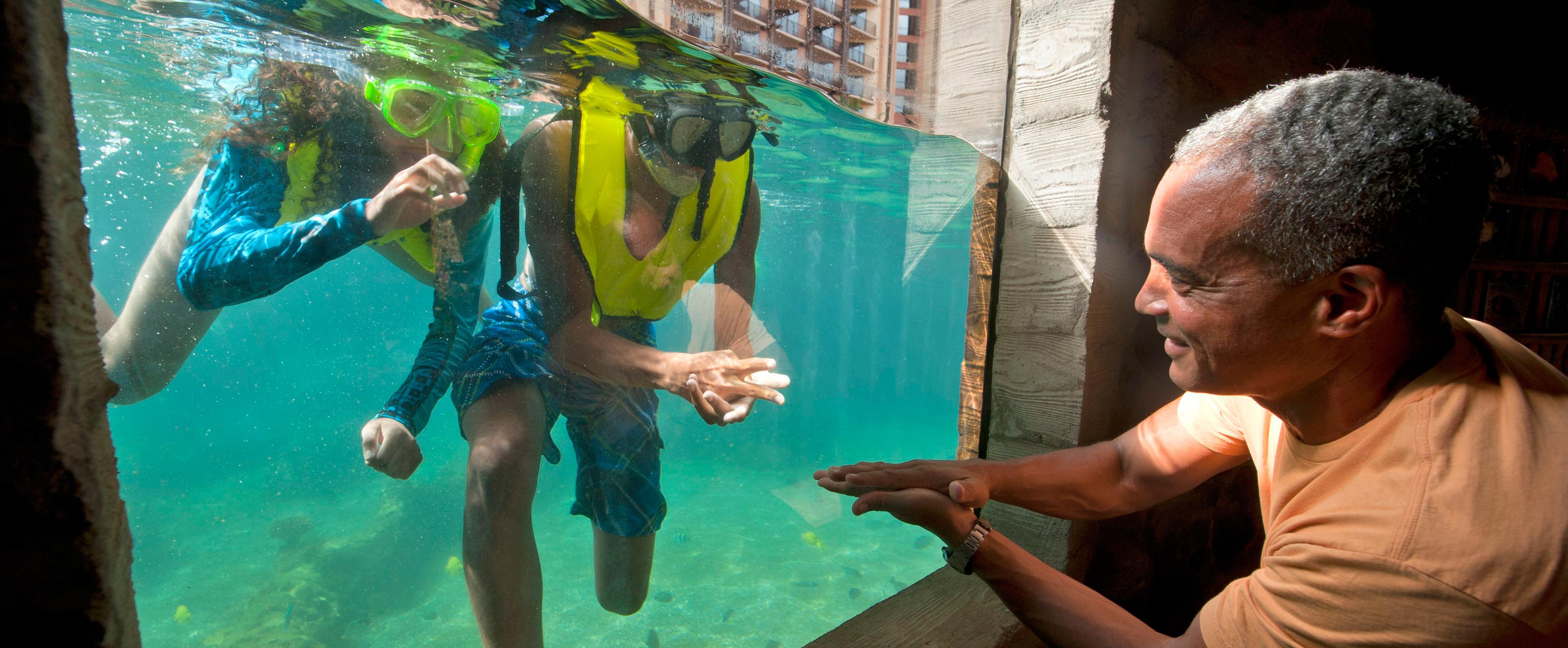 水族館のガラスを隔てて、水中でシュノーケリングを楽しむ子供たちとじゃんけんをする父親
