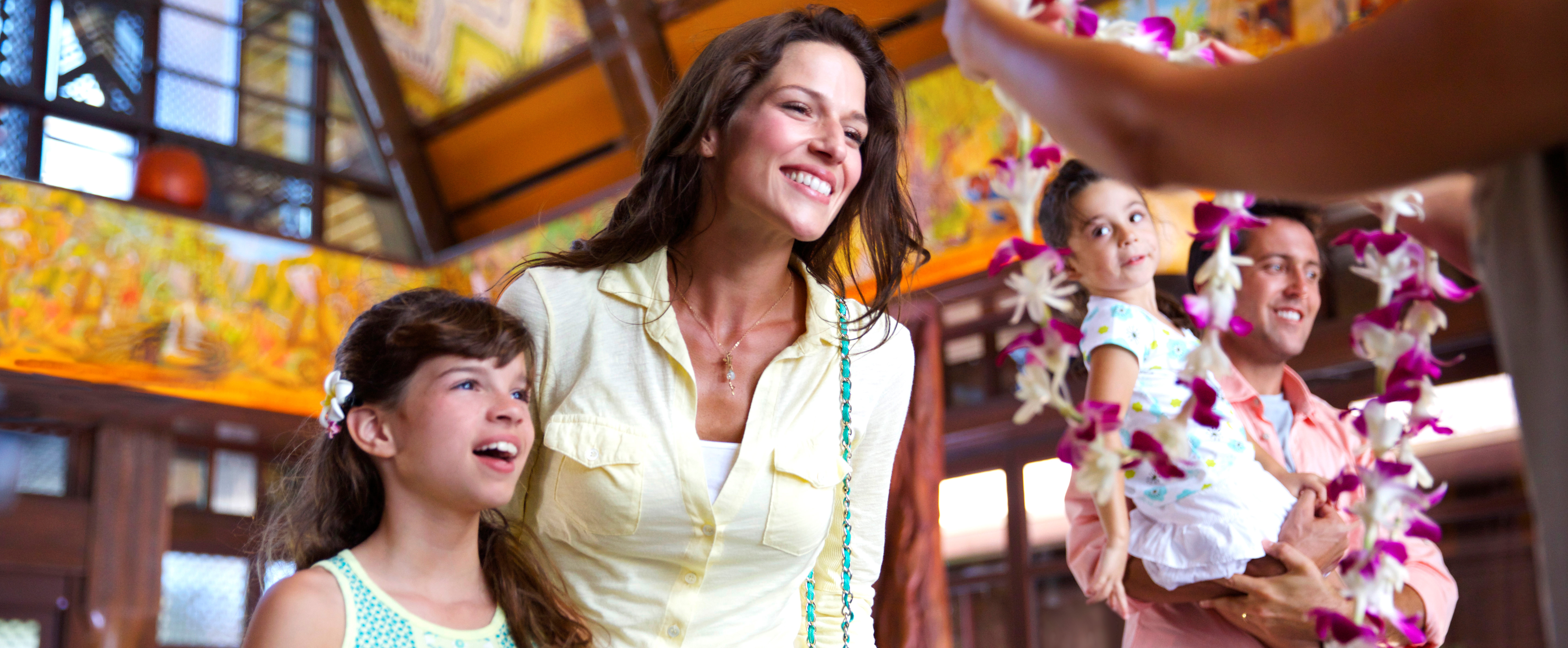 A mother and daughter are greeted with leis in the main lobby while a father holds their young daughter