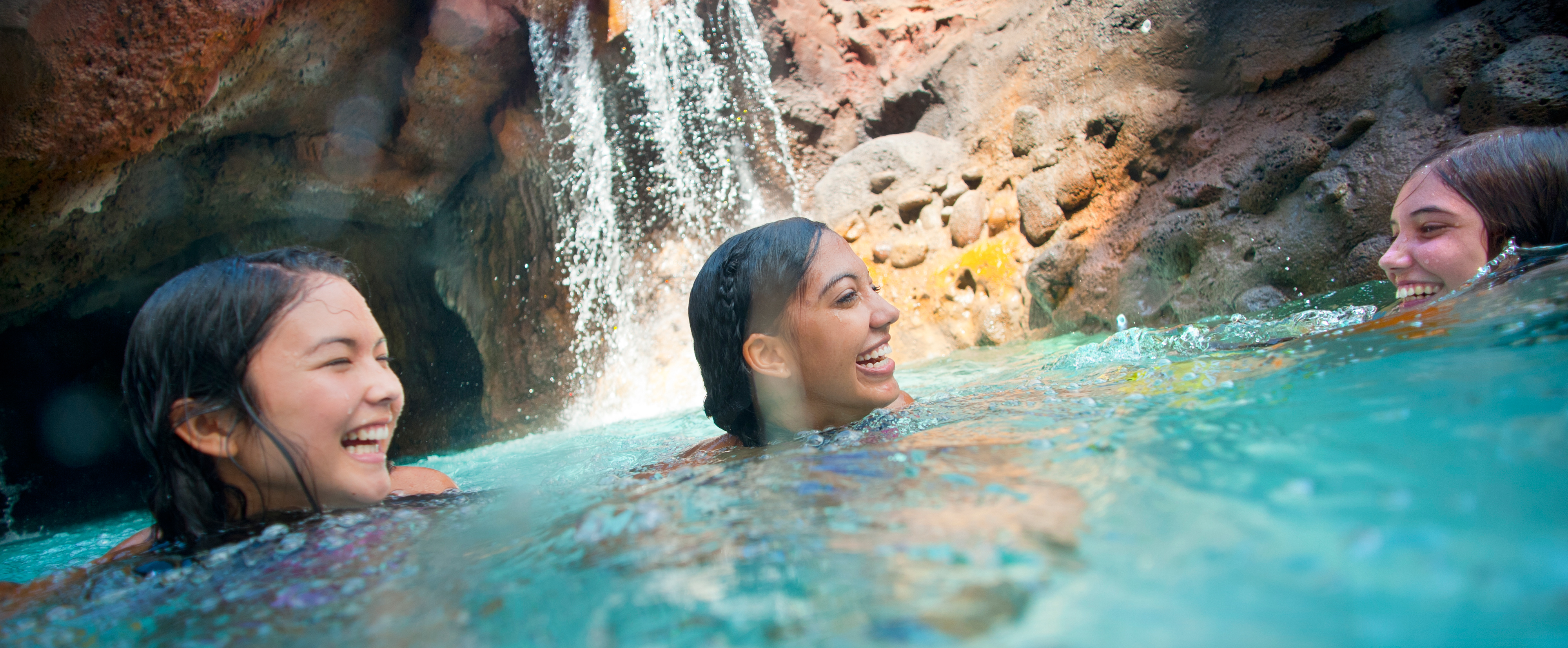 Three grinning teen girls are neck-deep in water in front of a grotto with a small waterfall