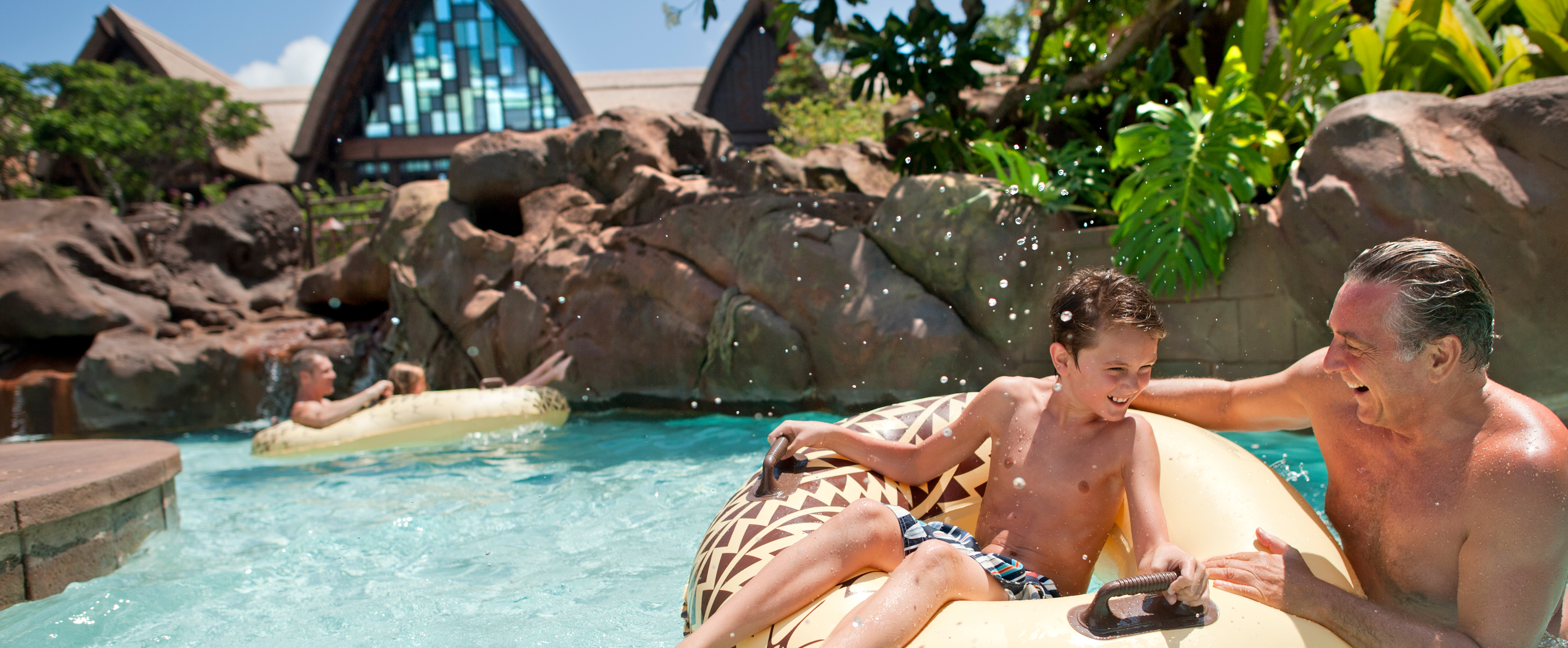 A young boy on an inner tube and his father play in a lazy river landscaped with rocks and tropical foliage