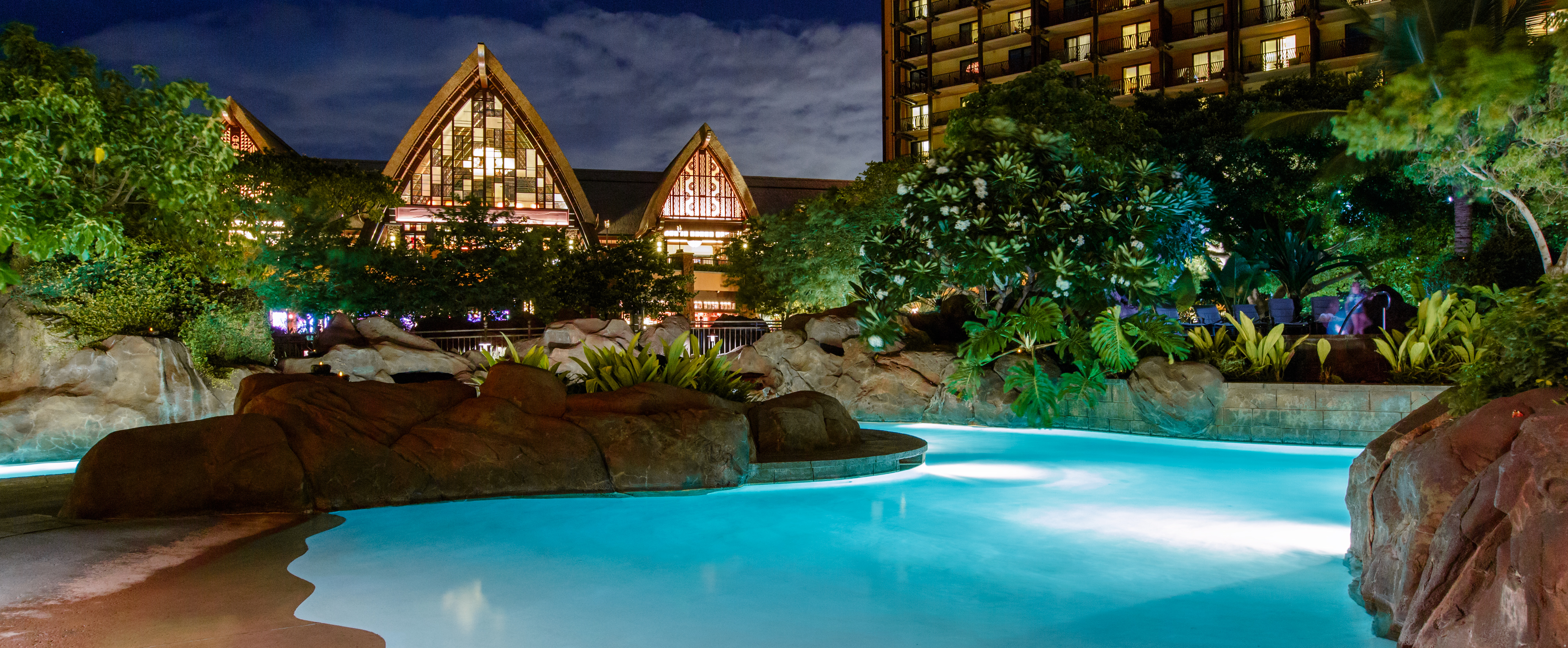 A section of the lazy river lit up at night, with the peaked roofs of the Resort's main building beyond