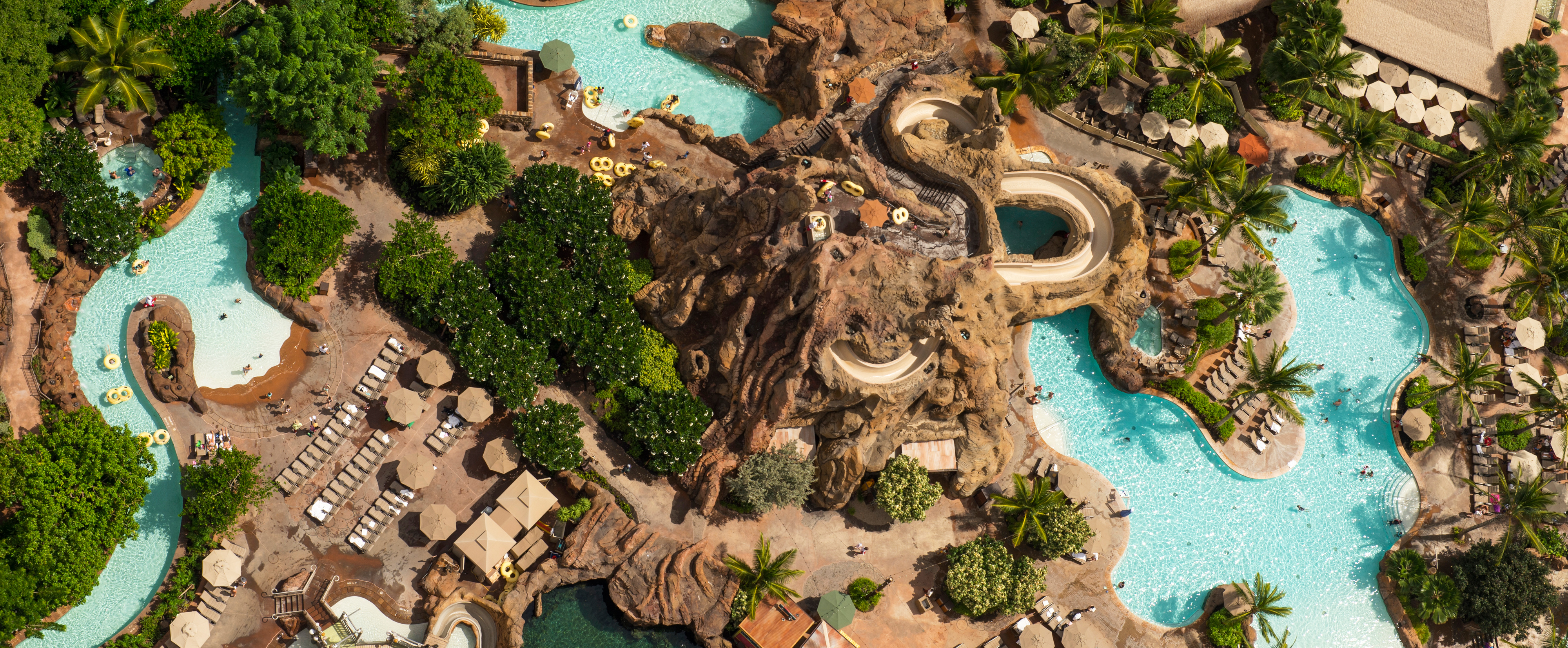 An aerial view of Waikolohe Stream, with a water slide, rock features, landscaping and sunbathing areas