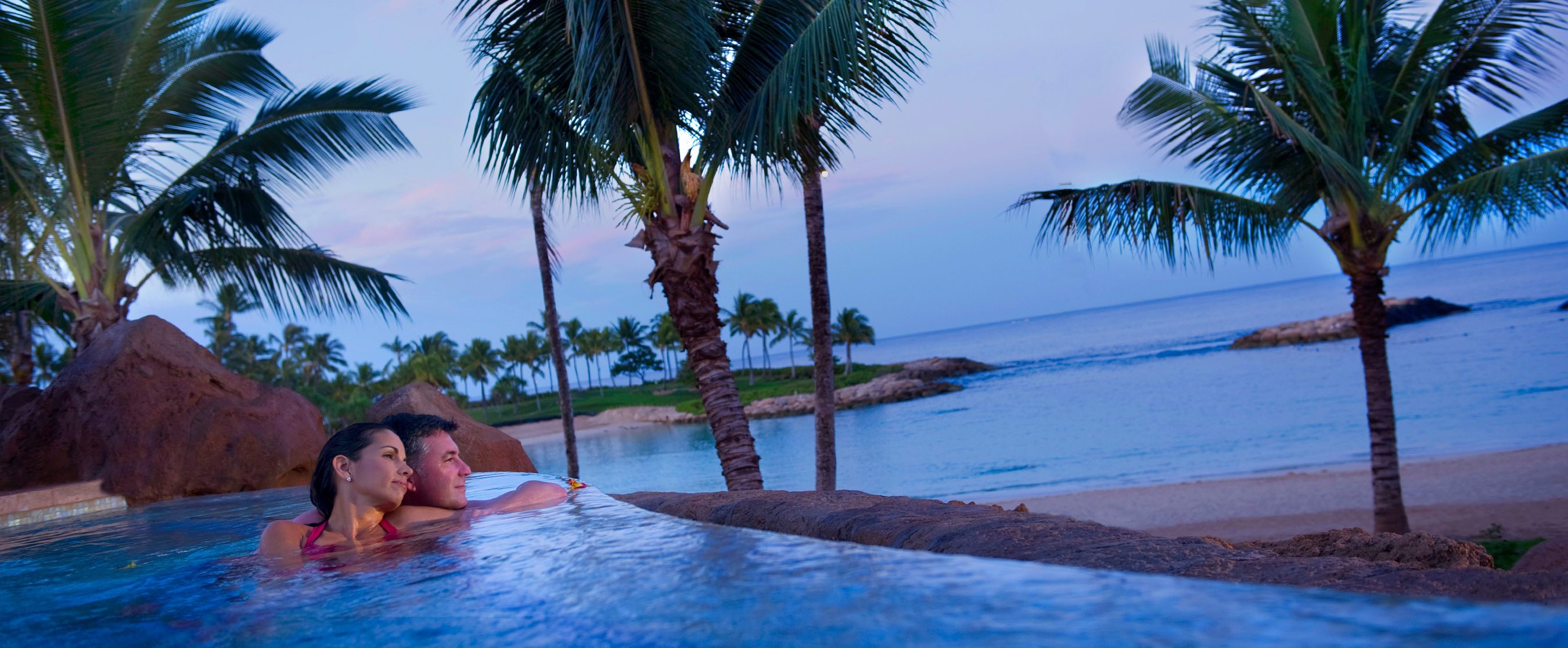 A mature couple leans toward one another in a whirlpool spa while looking longingly out to the ocean