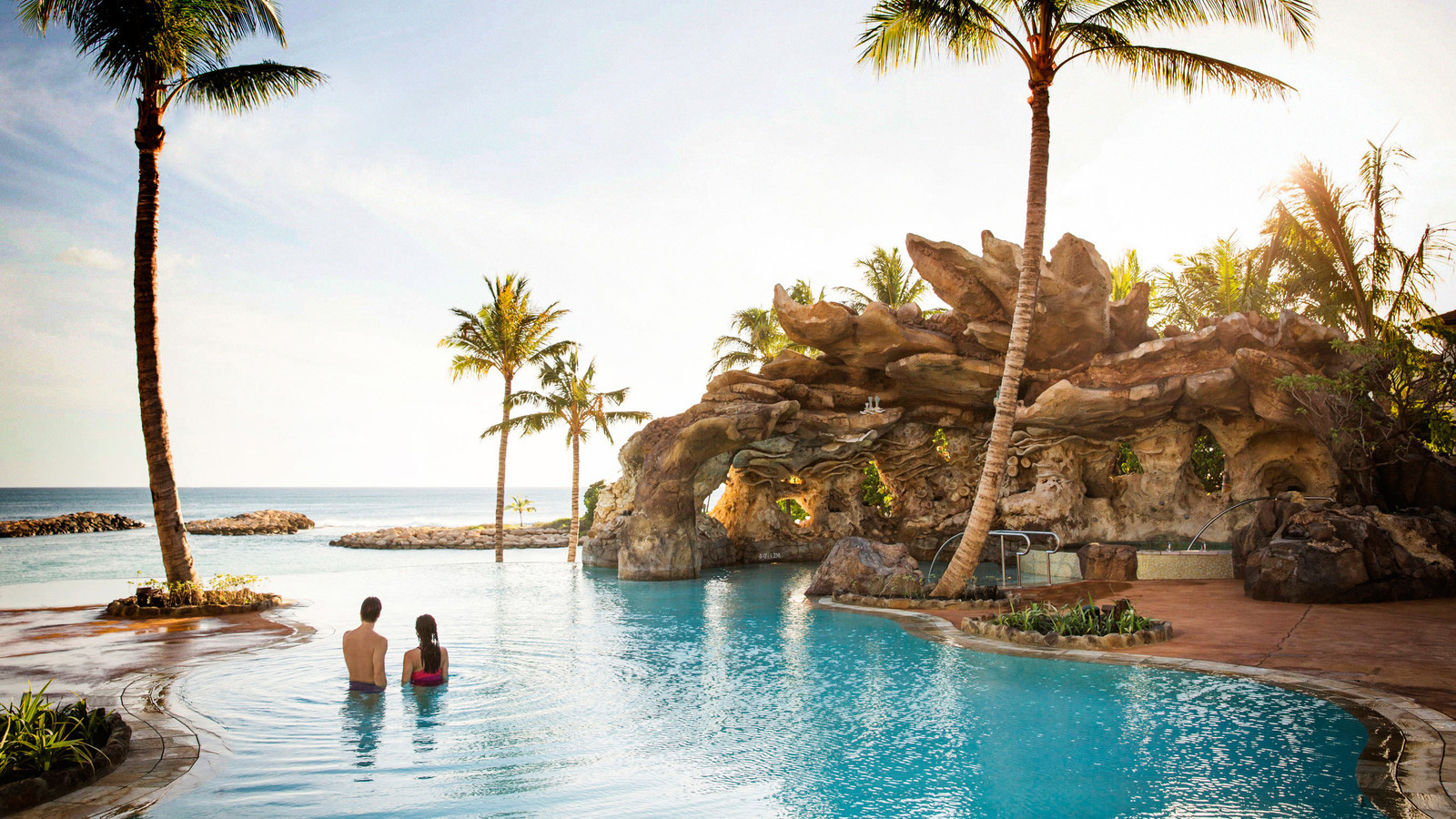 A couple in an infinity pool overlooking the ocean, with a whirlpool spa and grotto nearby
