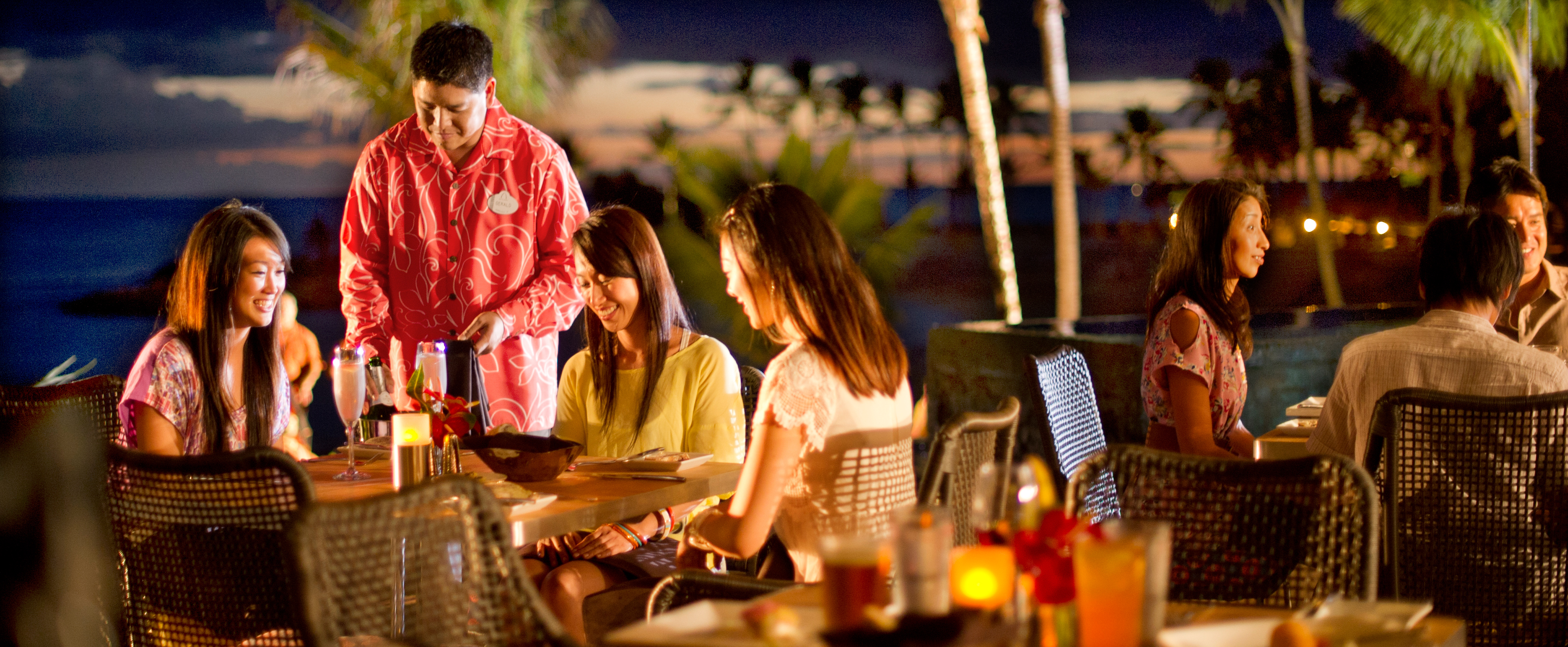 Three young women enjoy an outdoor evening meal with tableside Champagne service