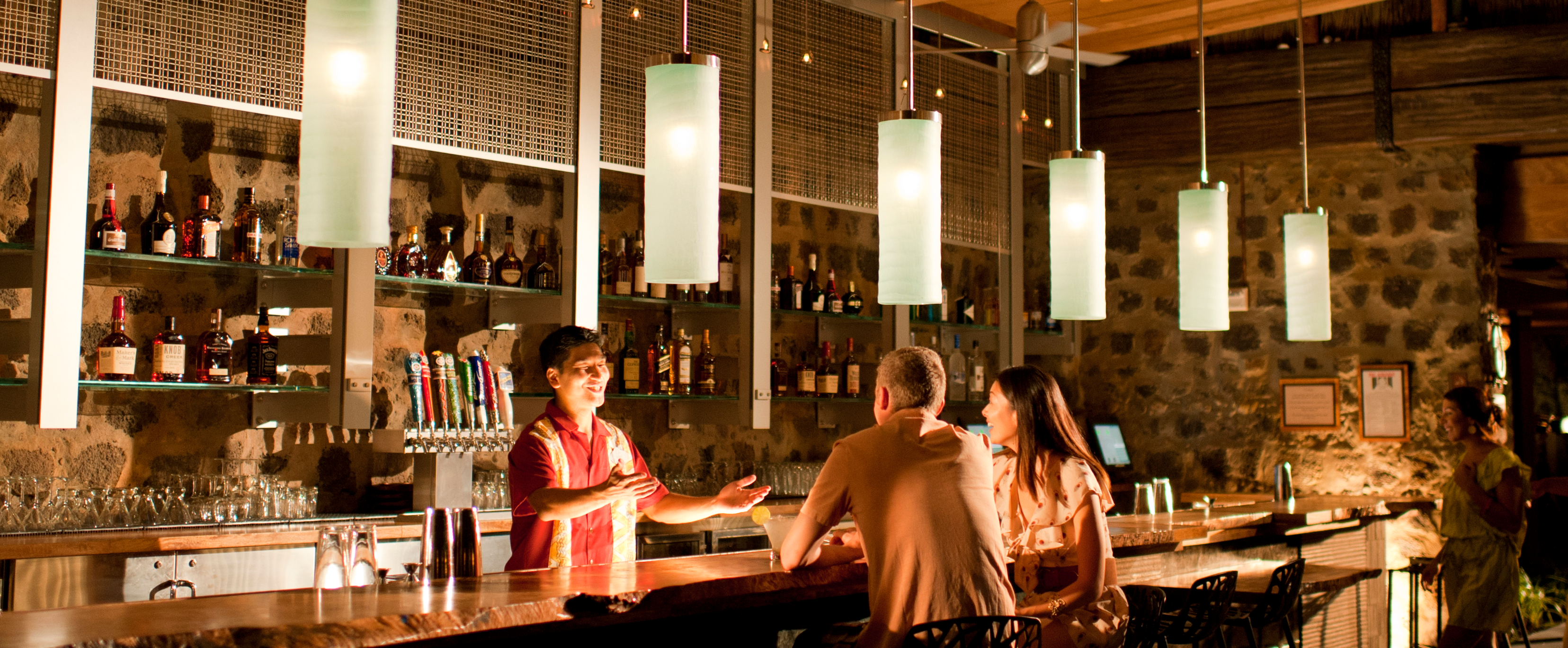 A smiling bartender gestures while talking to a couple seated at a bar with hanging light fixtures