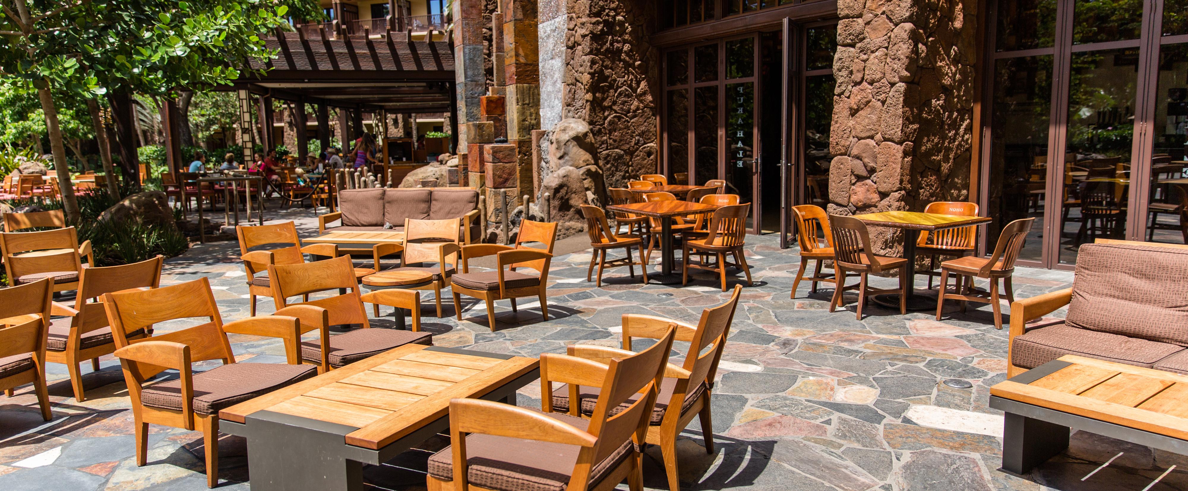 パティオの敷石の上に並ぶ屋外テーブルと 2 つのソファー