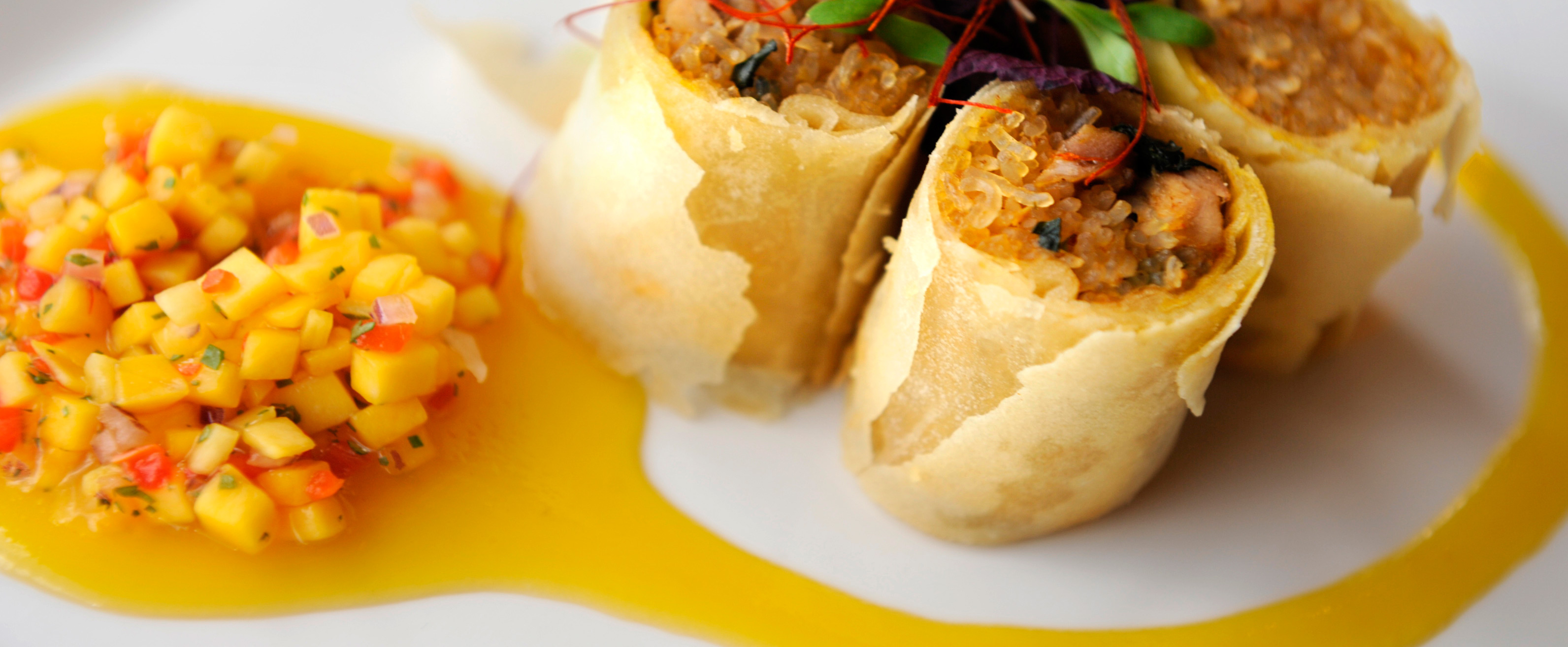 An egg roll cut into 3 pieces on a white plate garnished with mango salsa