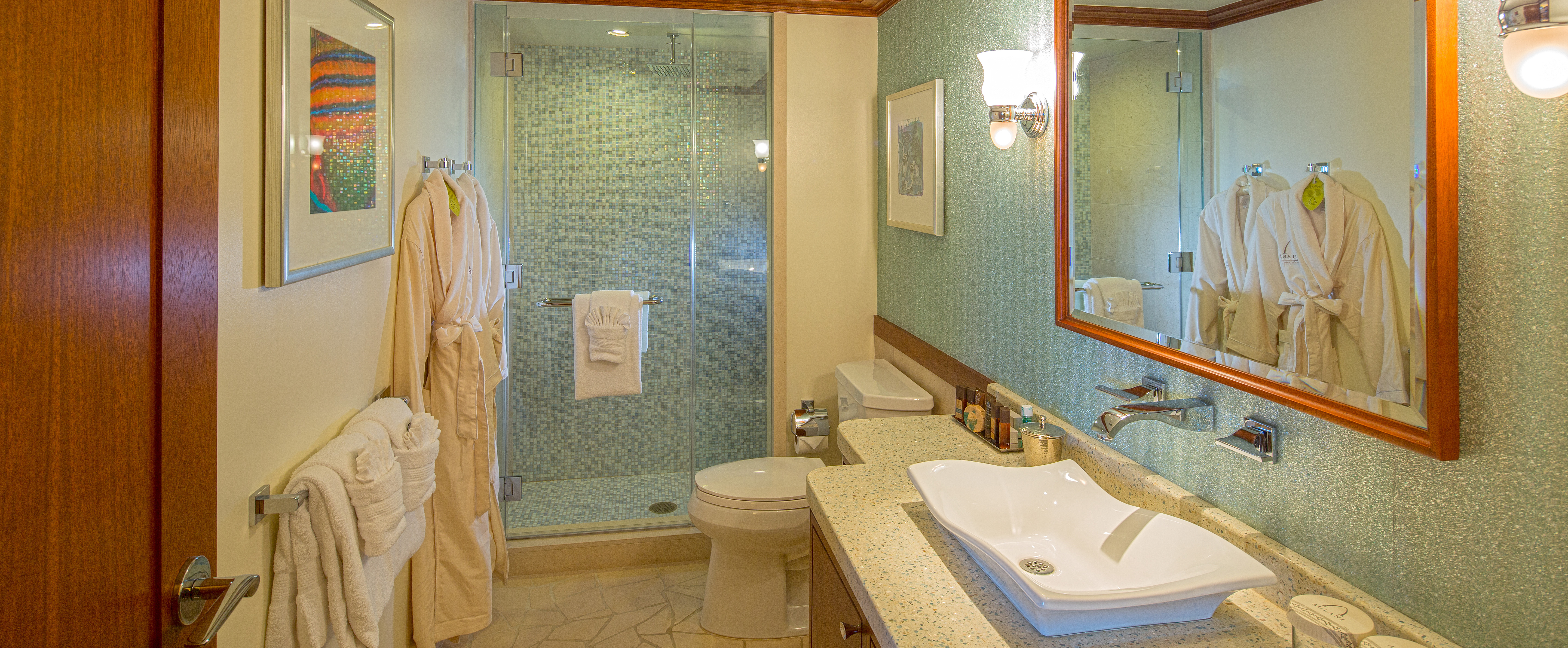 The bathroom in a deluxe 1-Bedroom Suite includes tile walls, stone countertops and walk in shower