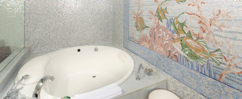 バスルームのバスタブ・エリアの壁を飾る水中の様子を描いたタイルのモザイク