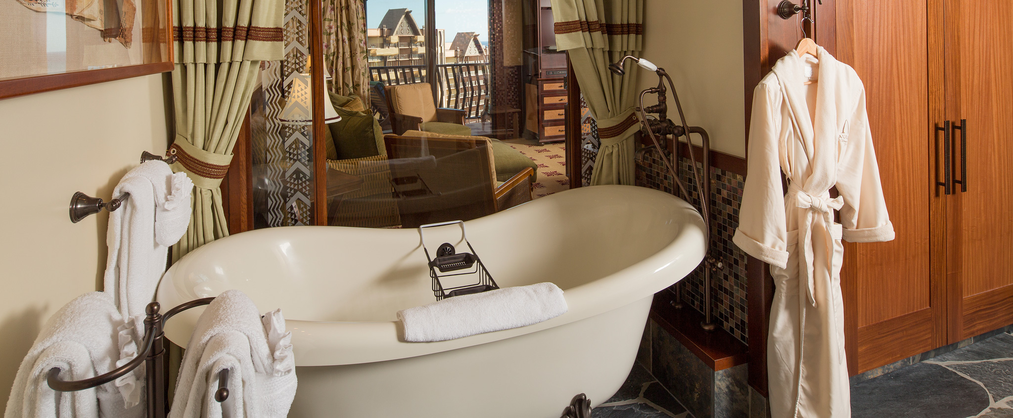 A bathrobe hangs next to a large claw foot tub in the 2-Bedroom Suite bathroom next to several towel bars