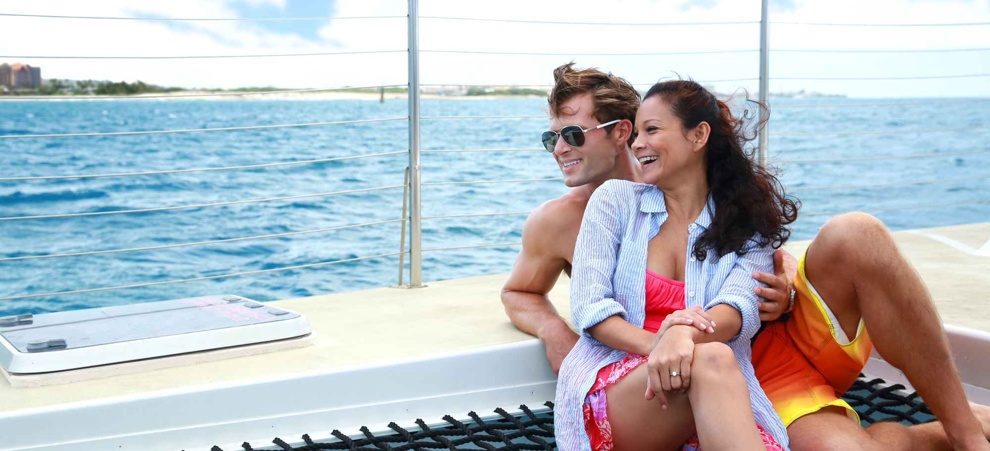 A smiling man and woman sit together on the deck of a catamaran at sea