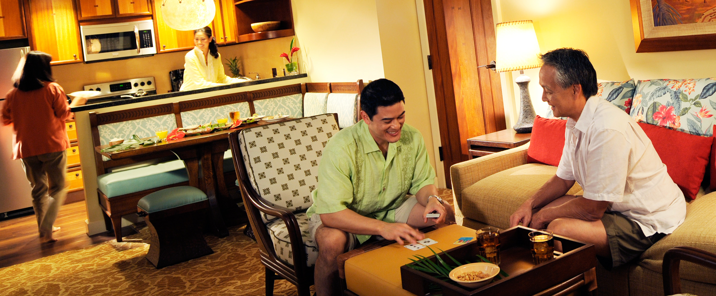 A family in the living area and kitchen of a 2-bedroom villa at Aulani