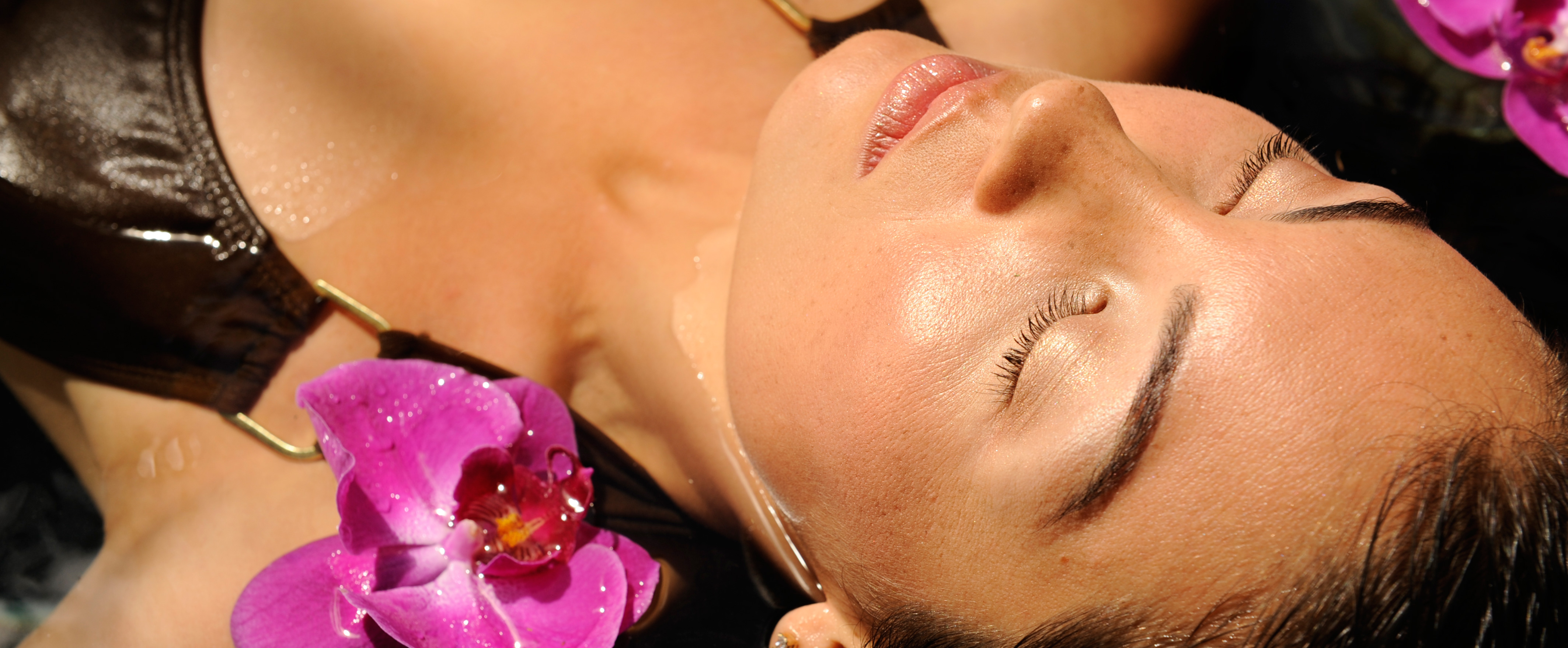 A woman lying in water with her eyes closed, with floating orchids on either side of her face