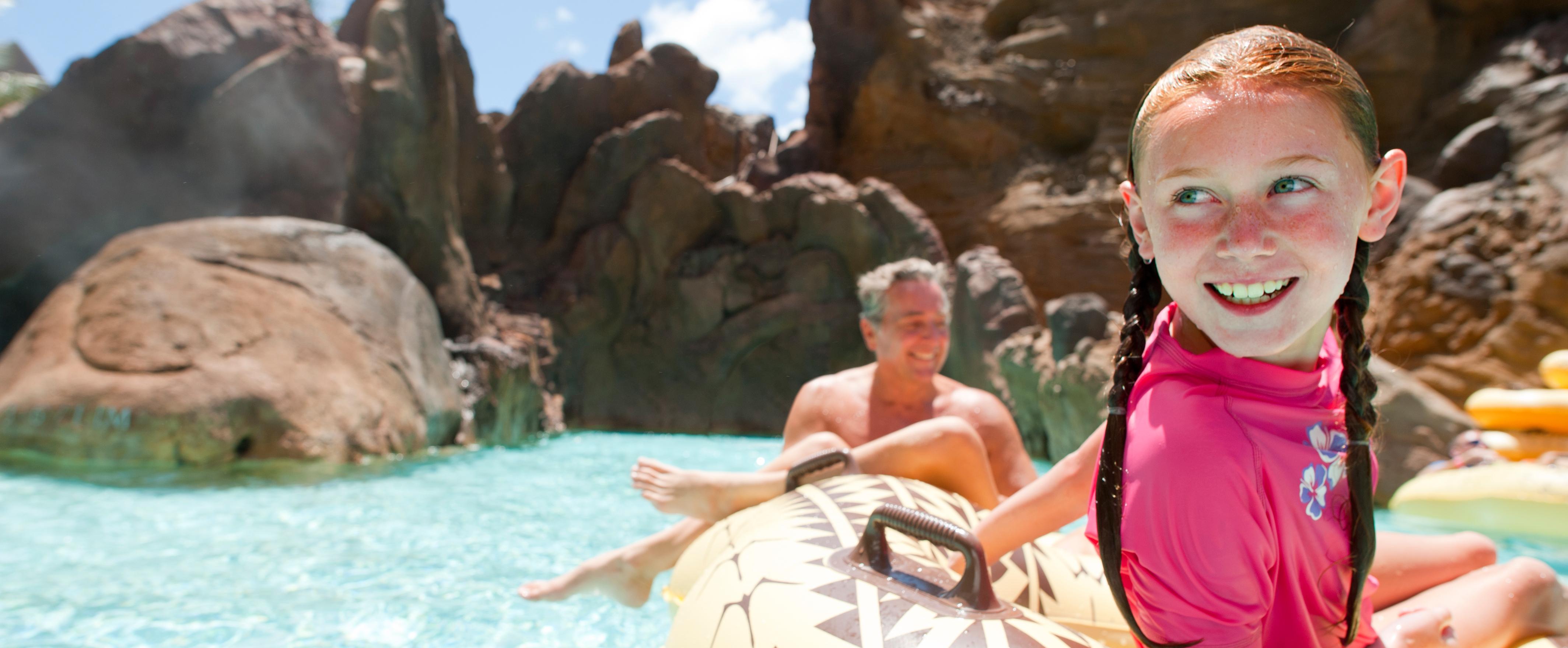 流れるプールで浮き輪で遊ぶ父と娘