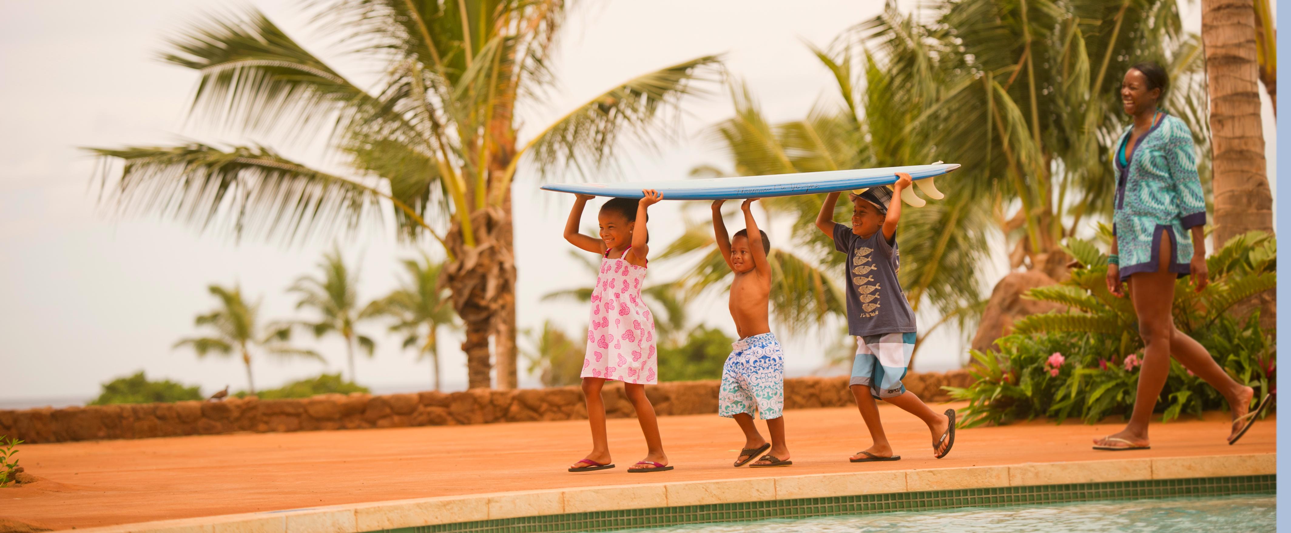 アウラニ・リゾートのプールエリアでサーフボードを運ぶ子供たち