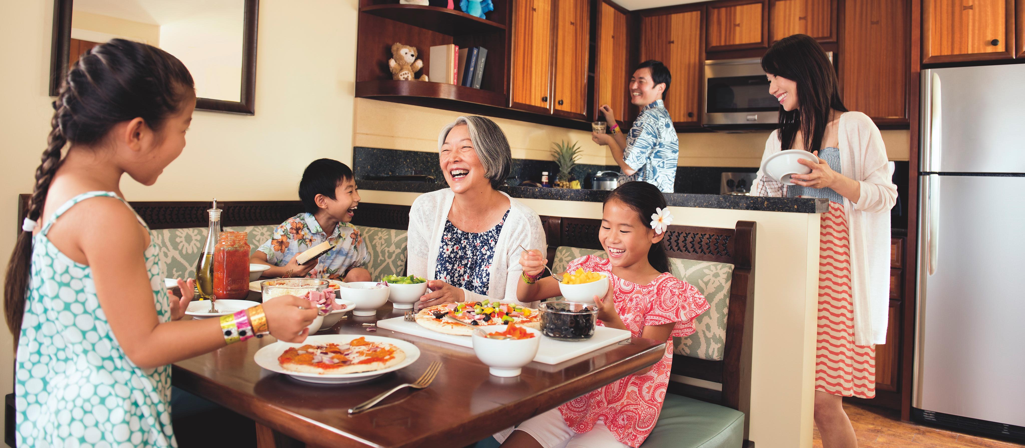 ヴィラのダイニングエリアとキッチンエリアでテーブルを囲んで食事を楽しむ 6 人の家族