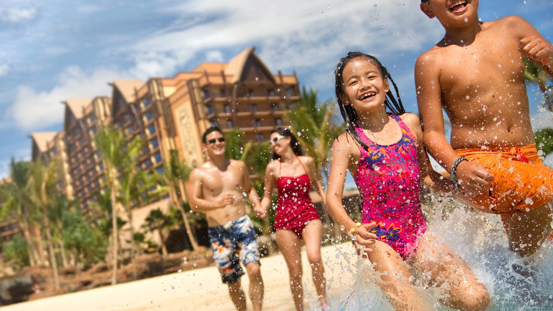 両親が後ろから見守る中、水しぶきをあげながらビーチを走る幼い兄妹
