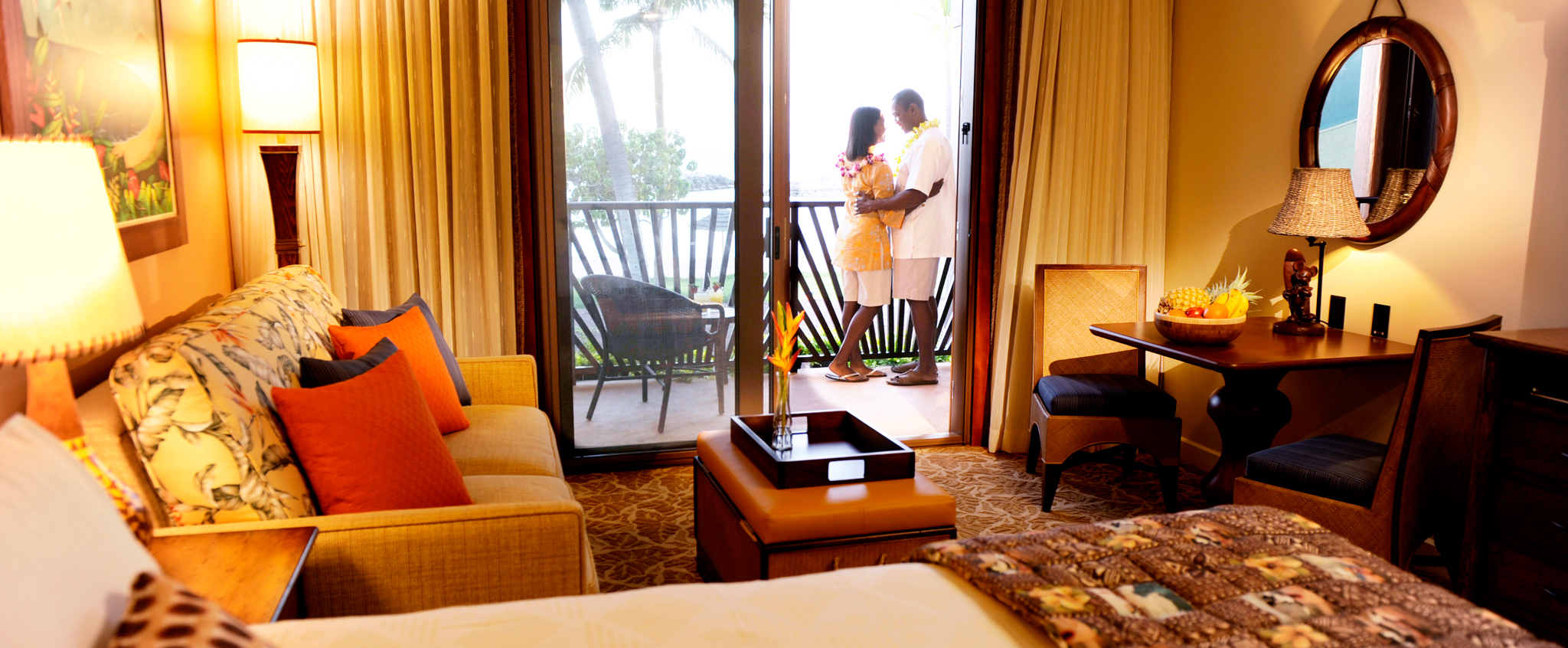 A couple embraces on the balcony of their hotel room featuring a large sitting area and Hawaiian décor