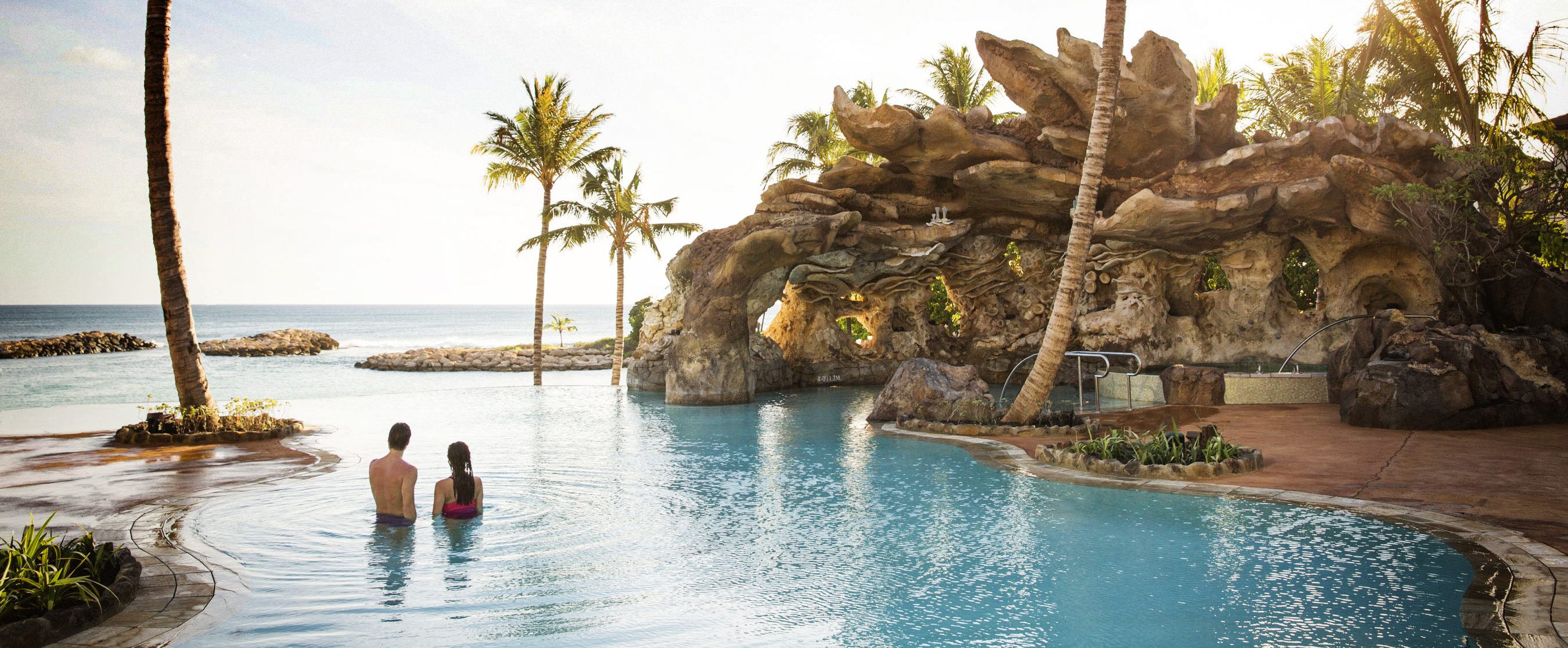 A couple in Ka Maka Grotto, the infinity-edge family pool at Aulani