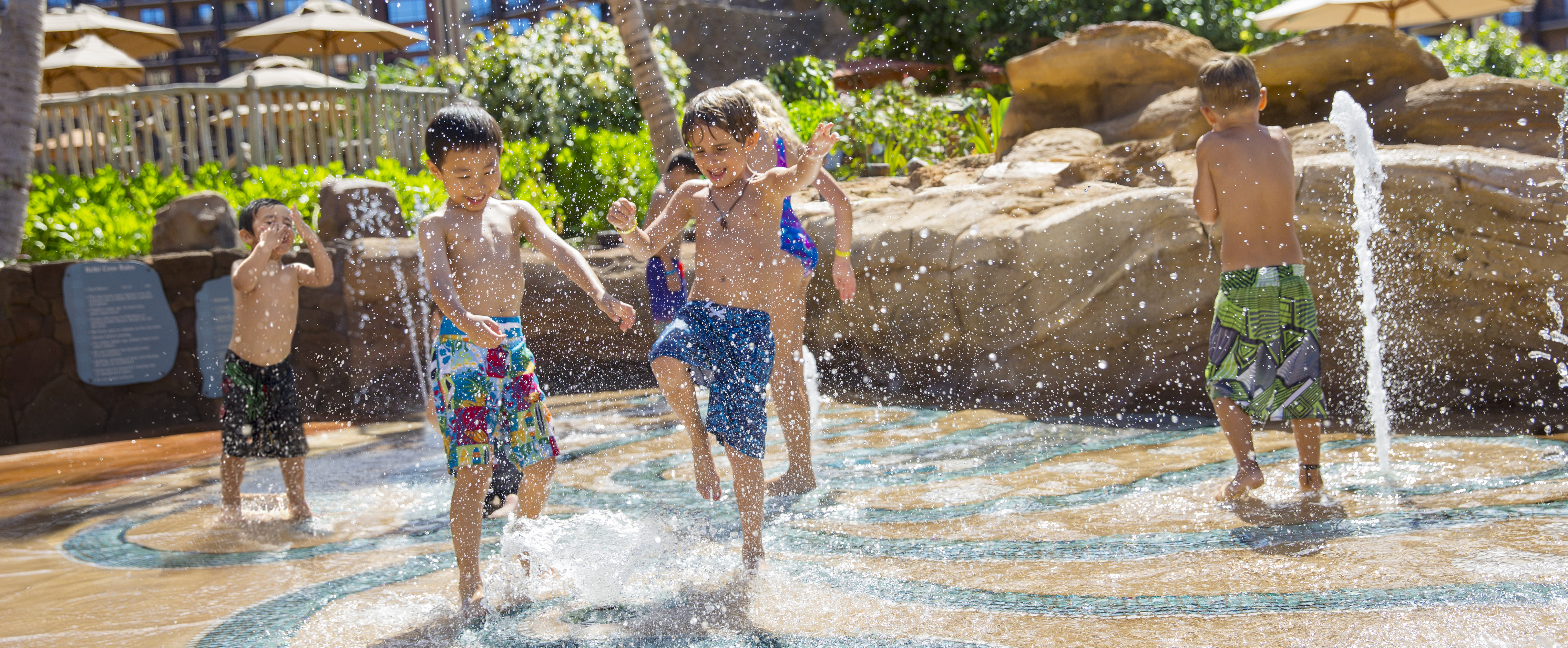 Kids playing in Keiki Cove, an interactive splash zone for young Guests at Aulani