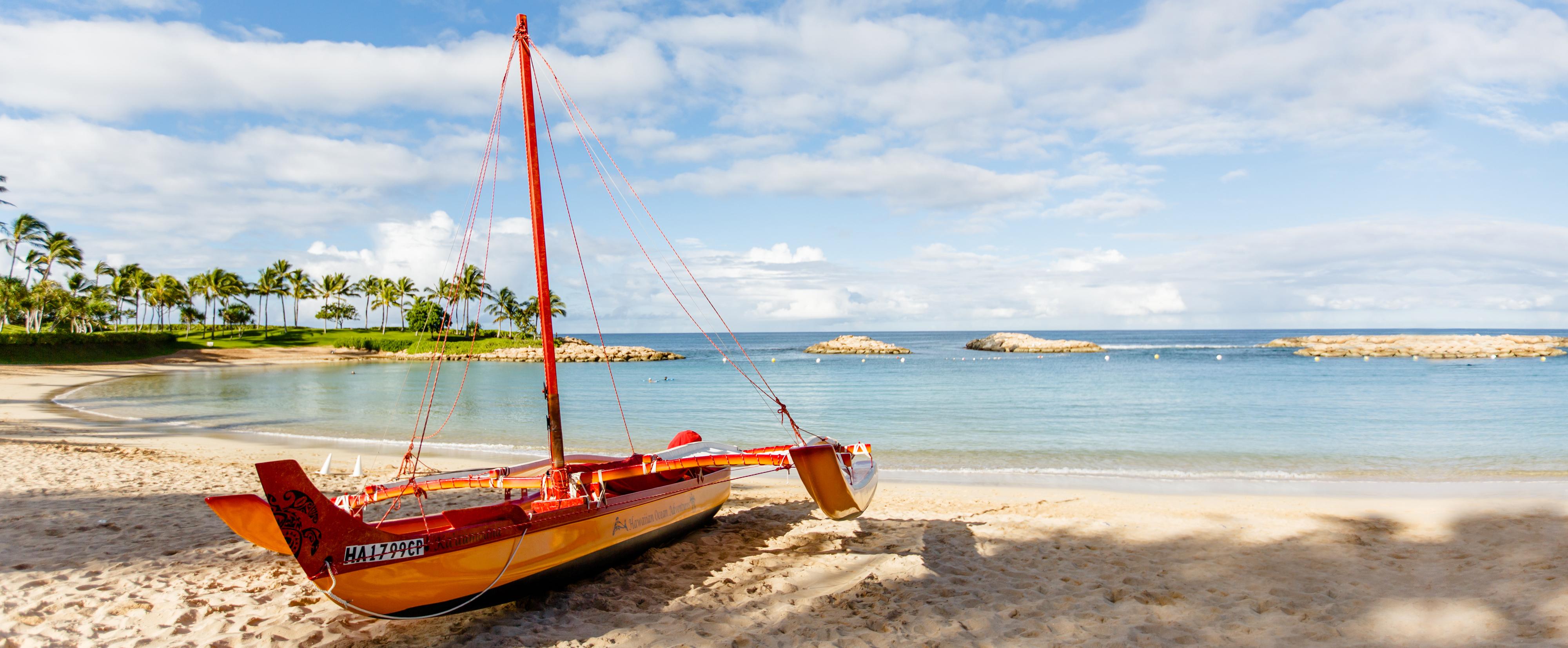 A Hawaiian sailing canoe on a sandy tropical beach, near the water's edge