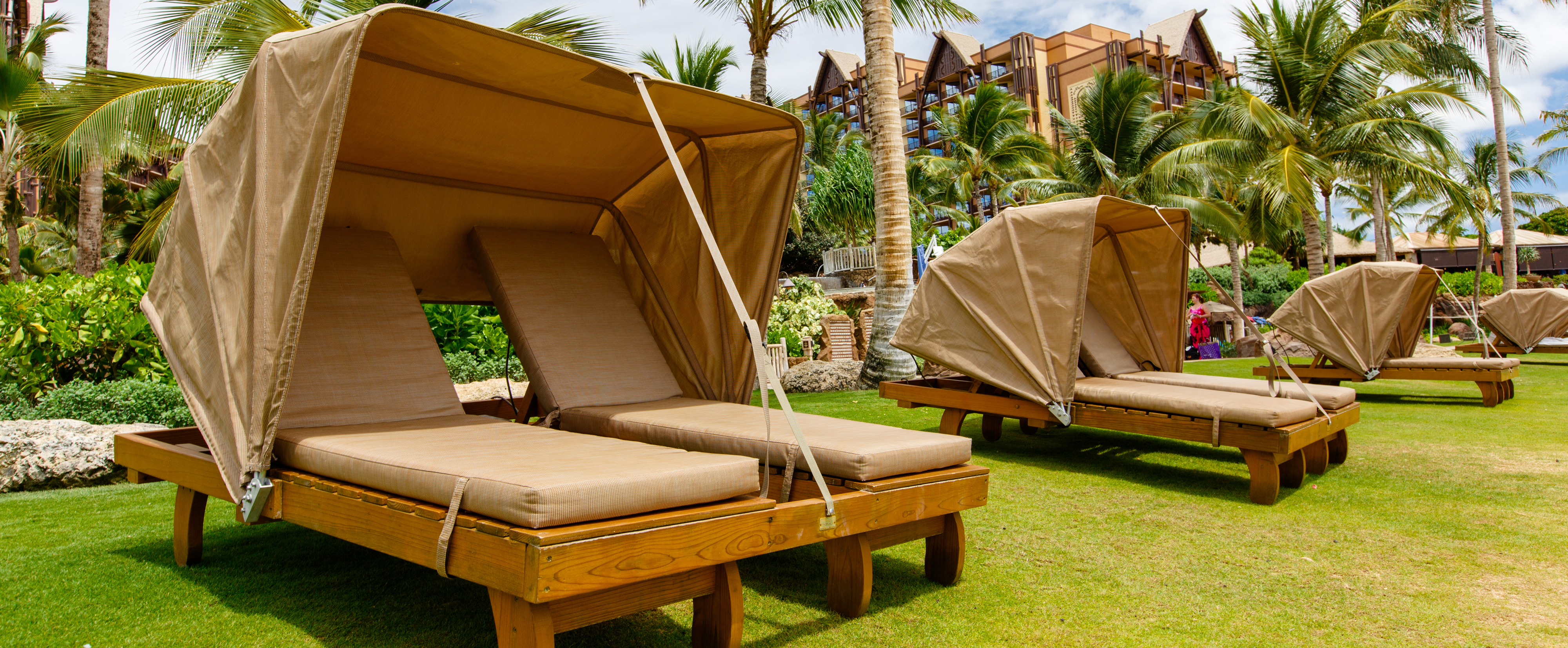 Four 2-person Casabella loungers with awnings on a lawn bordered by palm trees