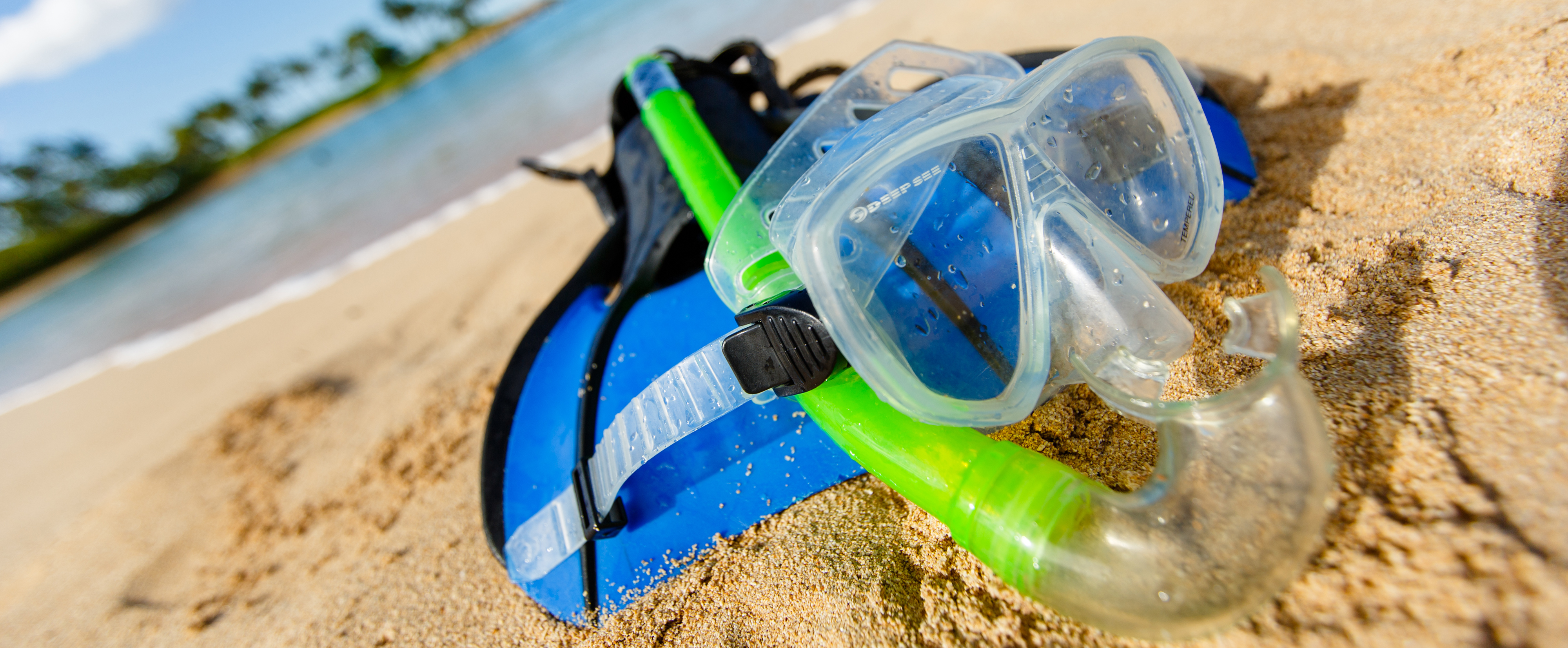 A snorkel mask and flippers on the shore of a sandy beach