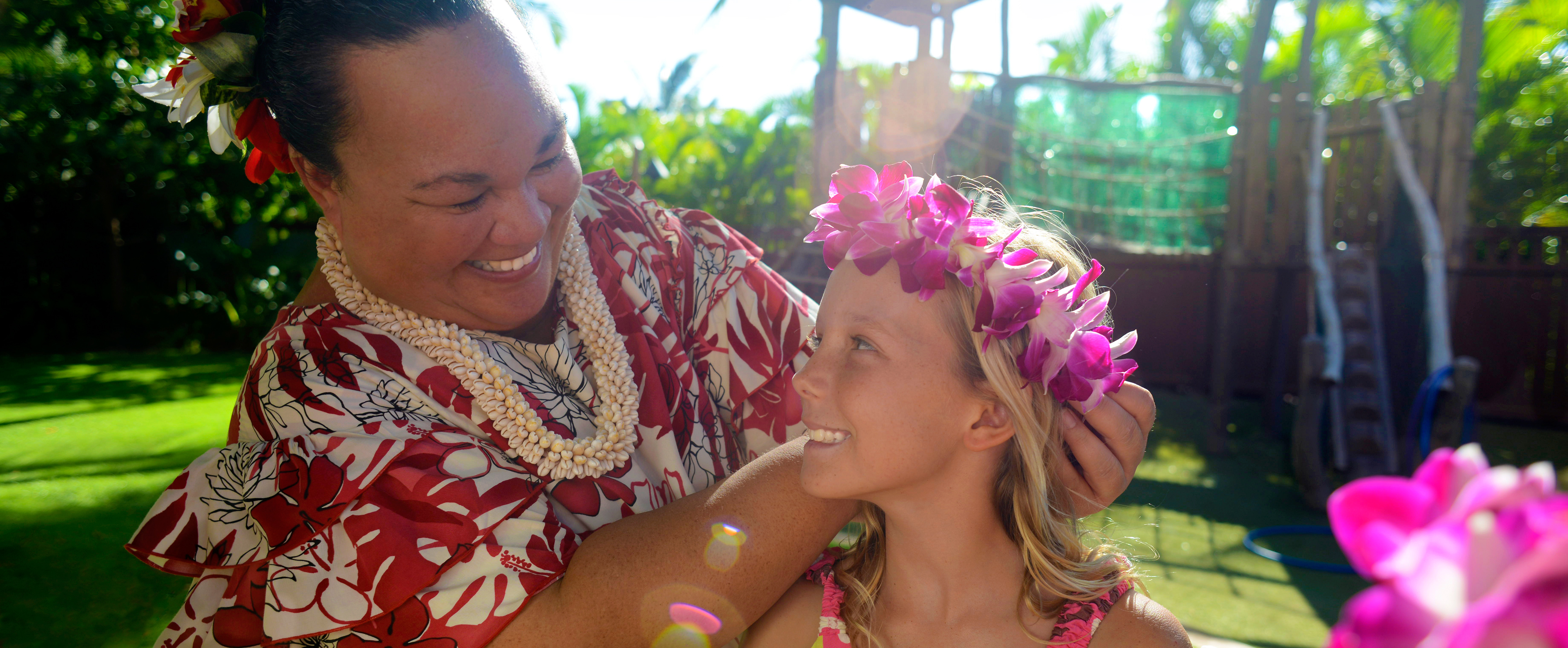 A smiling woman in Hawaiian garb puts a fuchsia orchid wreath on a young girl's head in a garden setting
