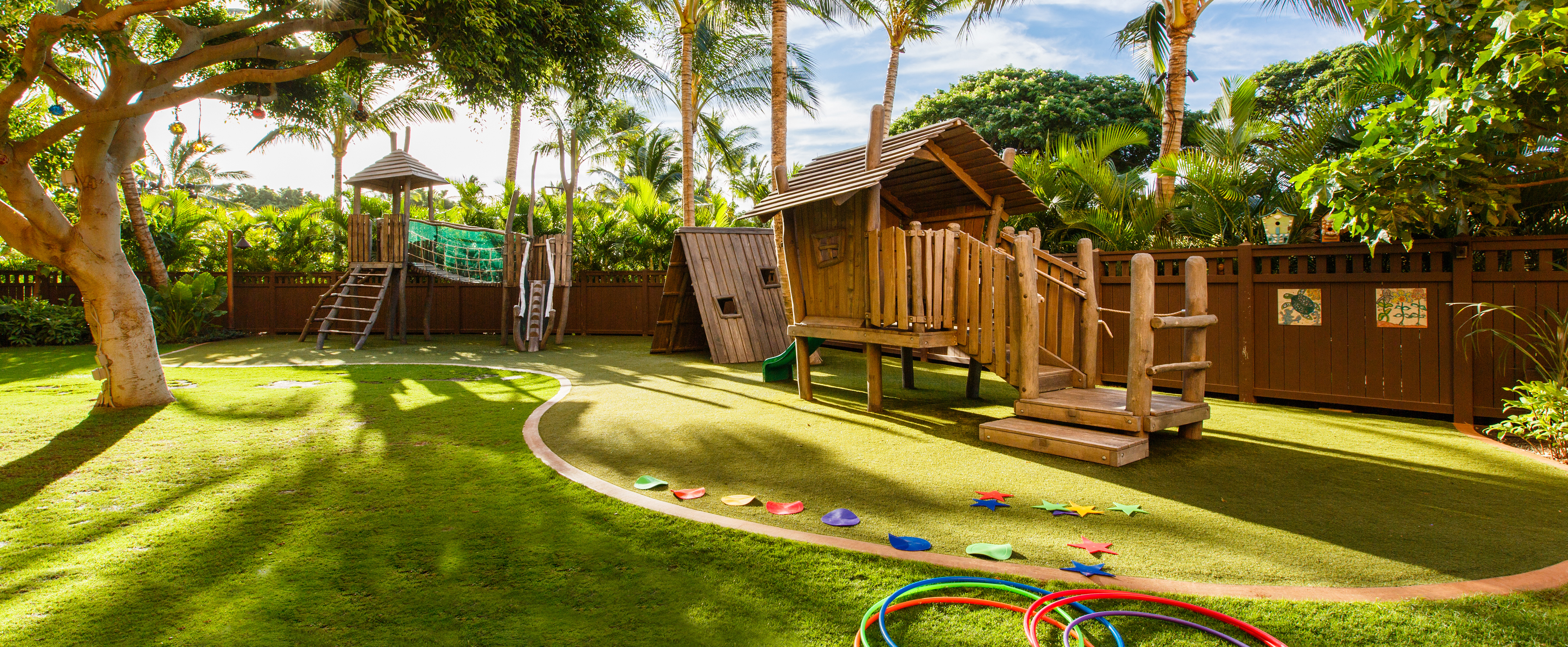 ... A Grassy Playground Area With 2 Wooden Climbing Structures, A Playhouse  And Hula Hoops On ...