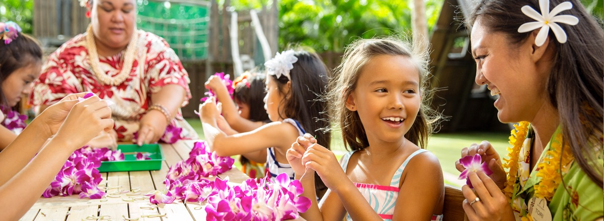Cast Members lead several young girls in a lei-making activity
