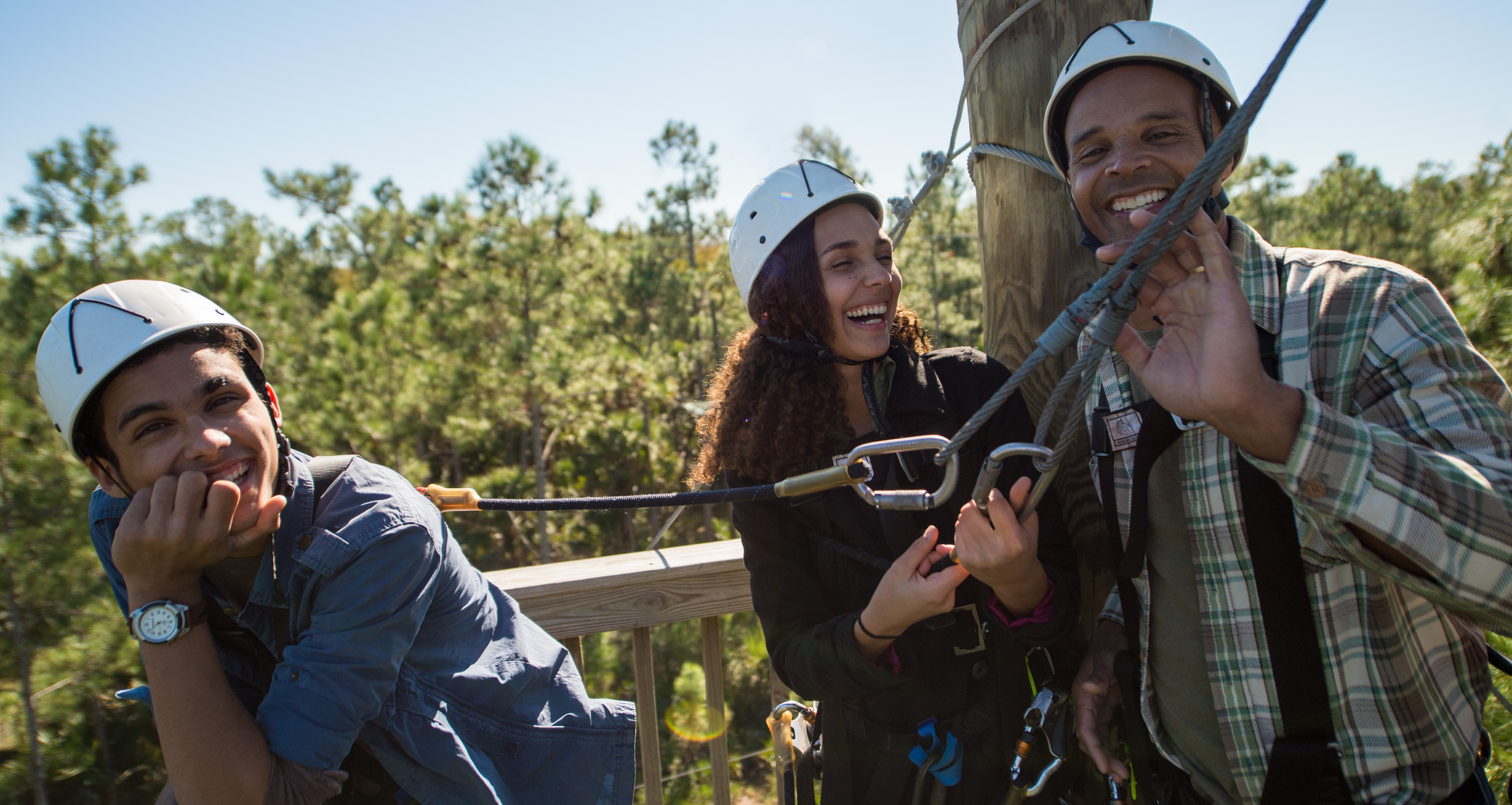 Two young men and a young woman in helmets wear harnesses attached to a zip line
