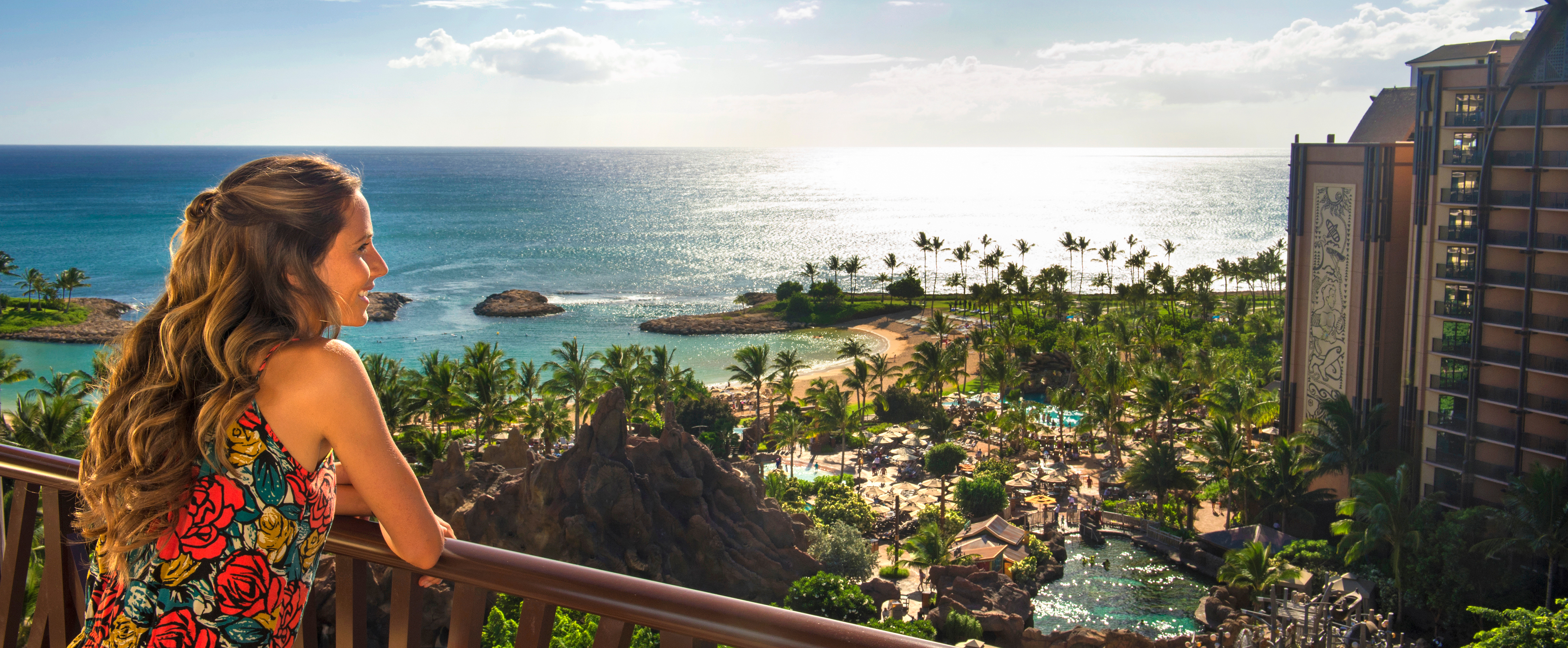 A woman in a dress stands on a balcony high above the pools and beachfront of Aulani Resort and Spa
