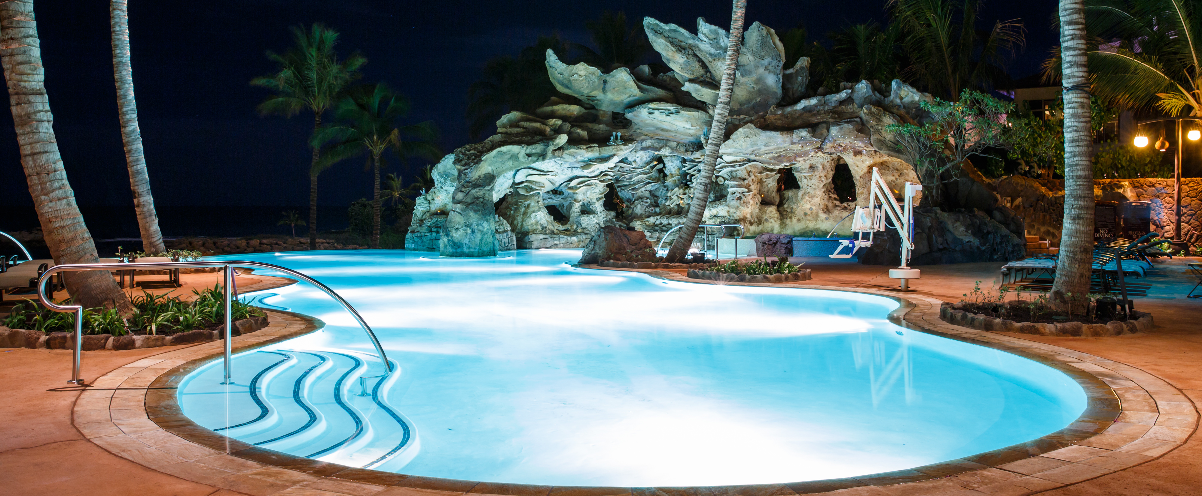 glittering lights illuminate the ka maka grotto oceanfront pool during an after dark experience - Swimming Pools With Grottos