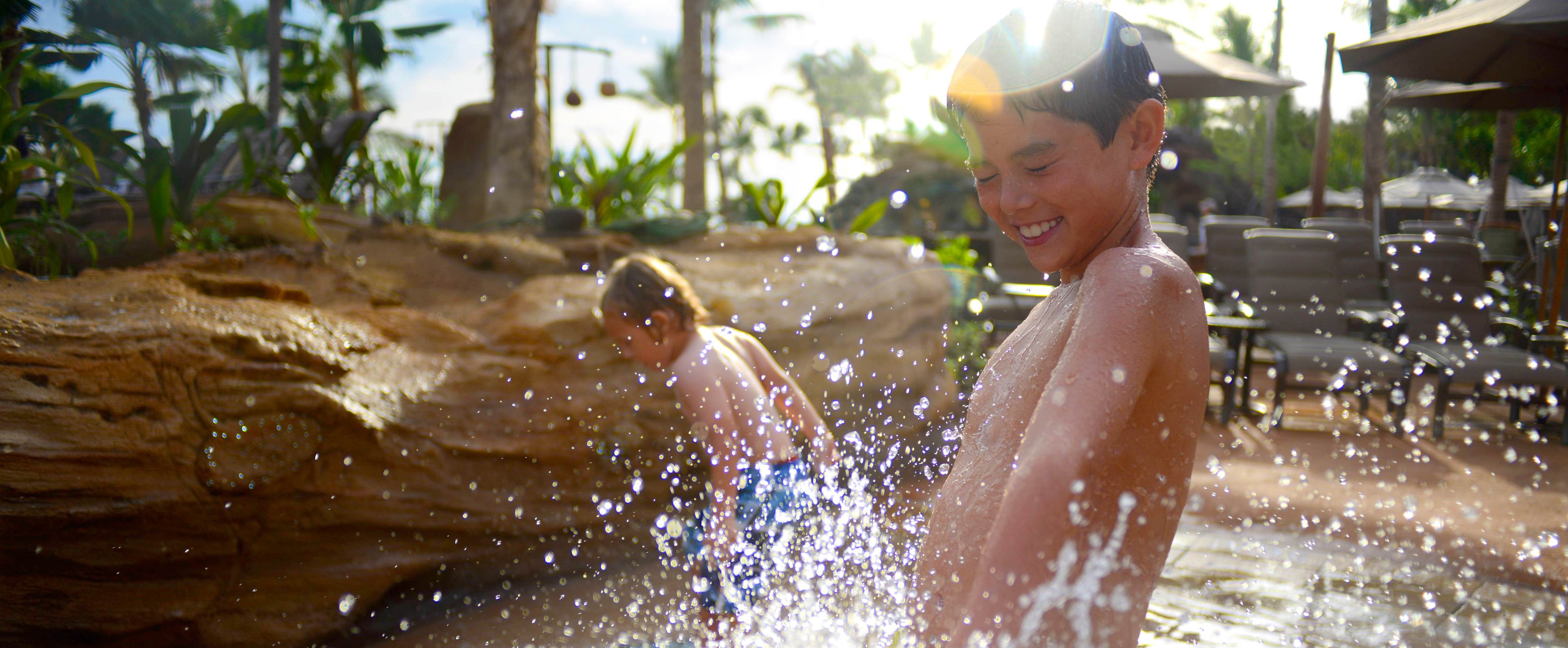 A boy braces himself against a spray of water in a play area surrounded by rocks as another boy plays