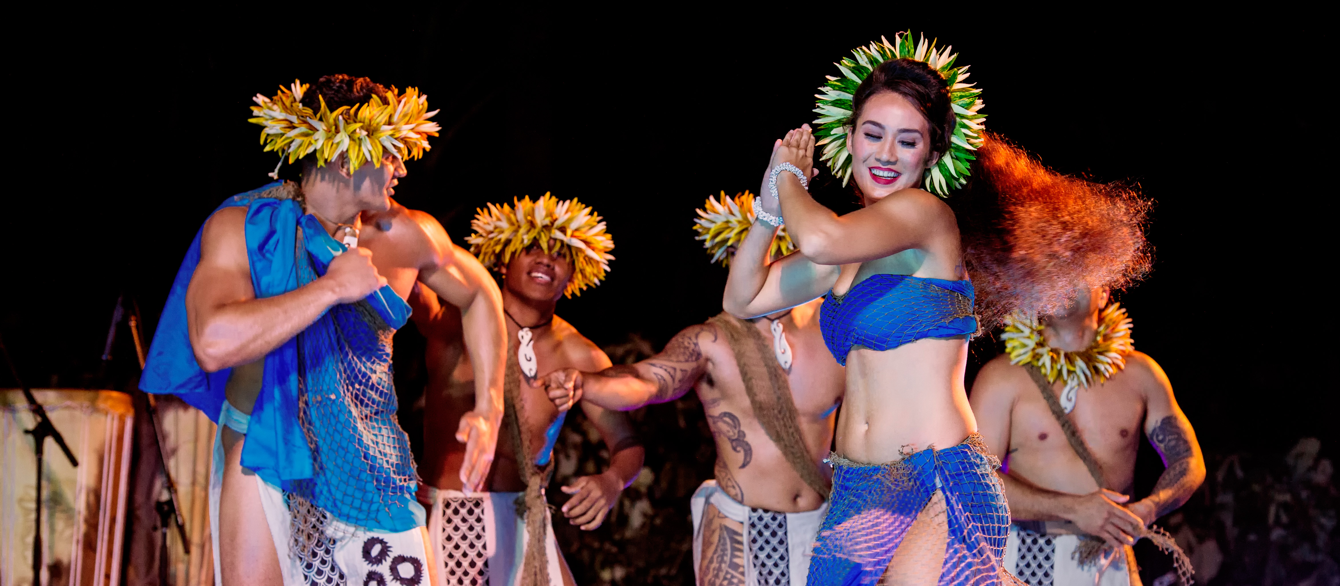 A pair of dancers dressed in beautiful outfits and flowery head dresses perform a dance as three male dancers look on behind them.