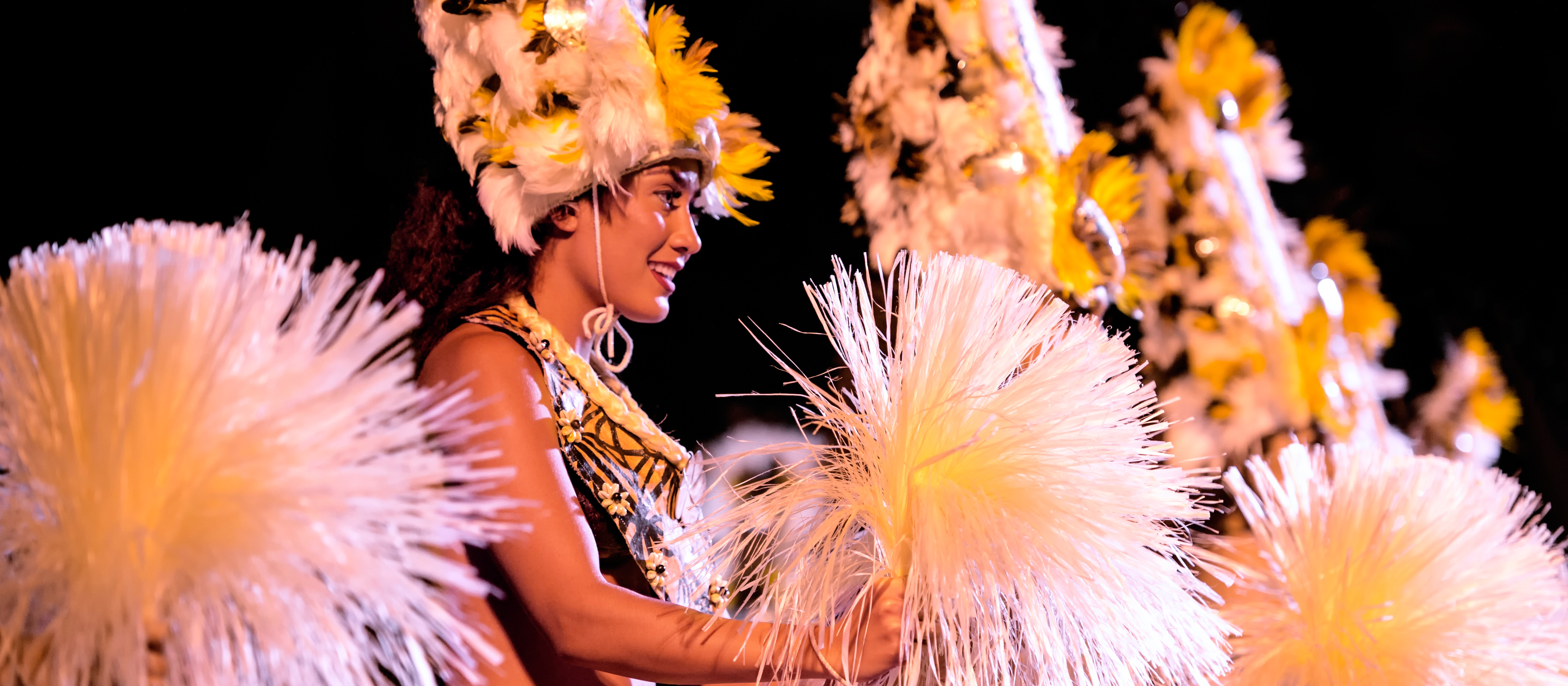 A female dancer holding grassy pom-poms and wearing traditional Hawaiian dress, including a hat made of feathers, performs a Hawaiian dance at the Ka Wa'a Luau.