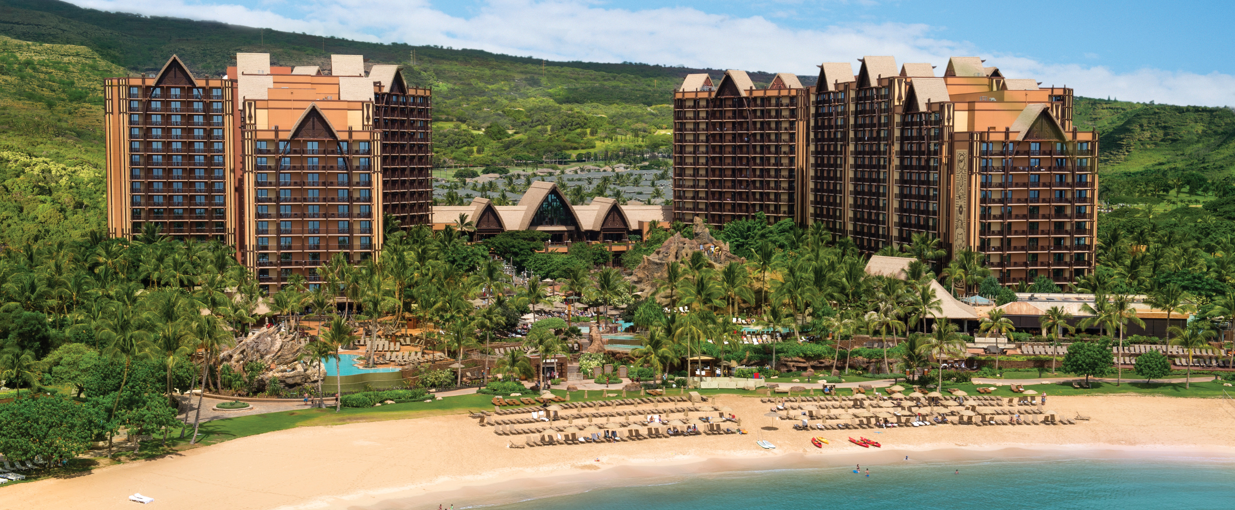 The buildings, pools and beachfront of Aulani Resort set against the Oahu hills