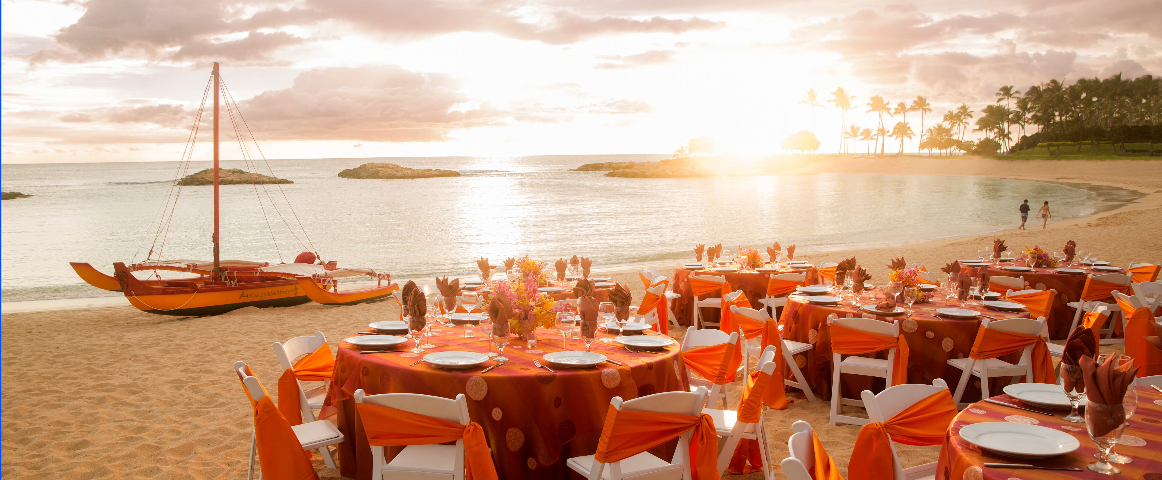 Festively Set Tables And Chairs Are Grouped In The Sand Along Beachfront