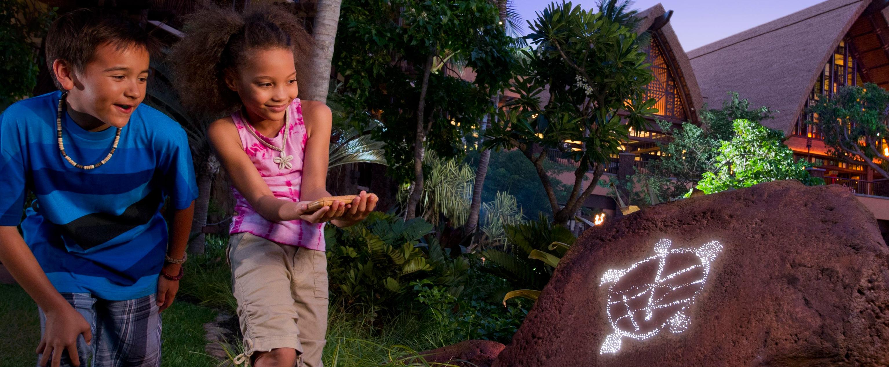 木や草に隠れた岩に描き出された、カメの記号を見つける少年と少女