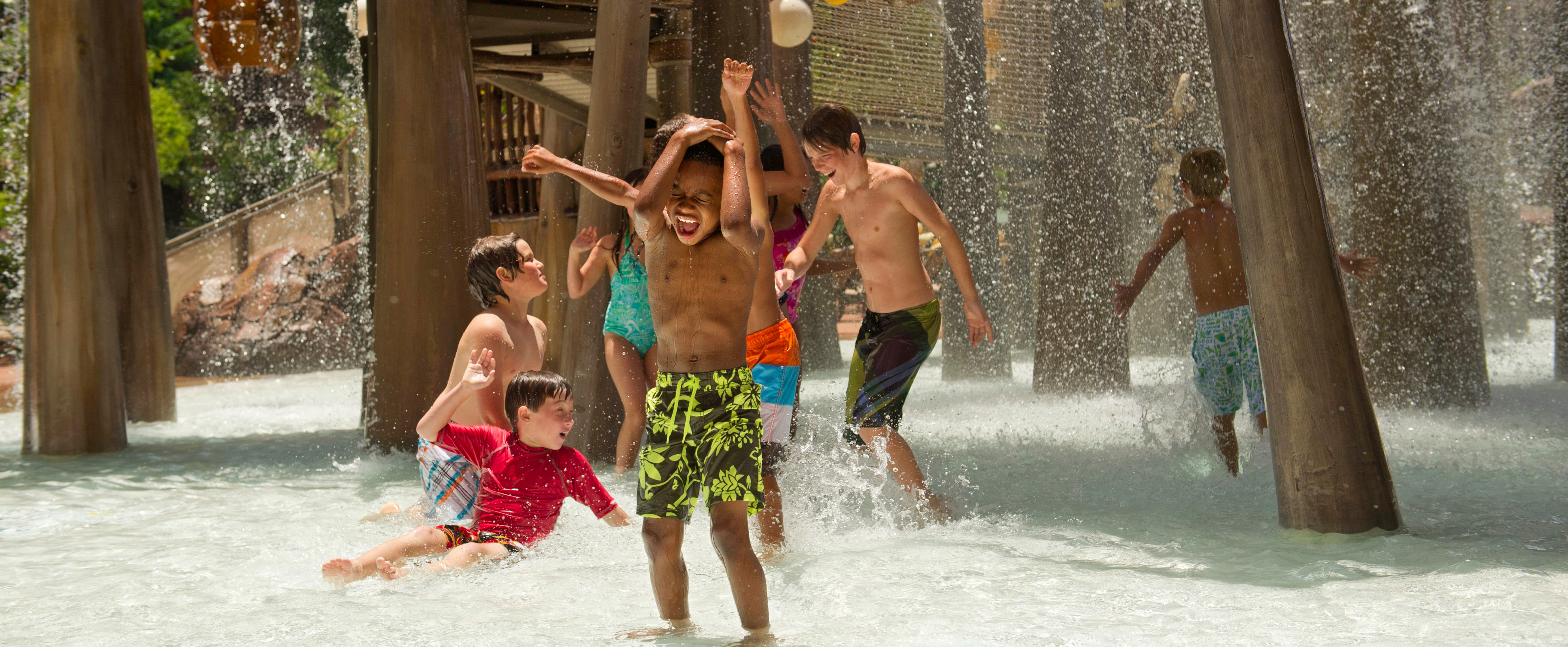 Children of all ages splashing about as water pours down onto them from the Menehune Bridge above