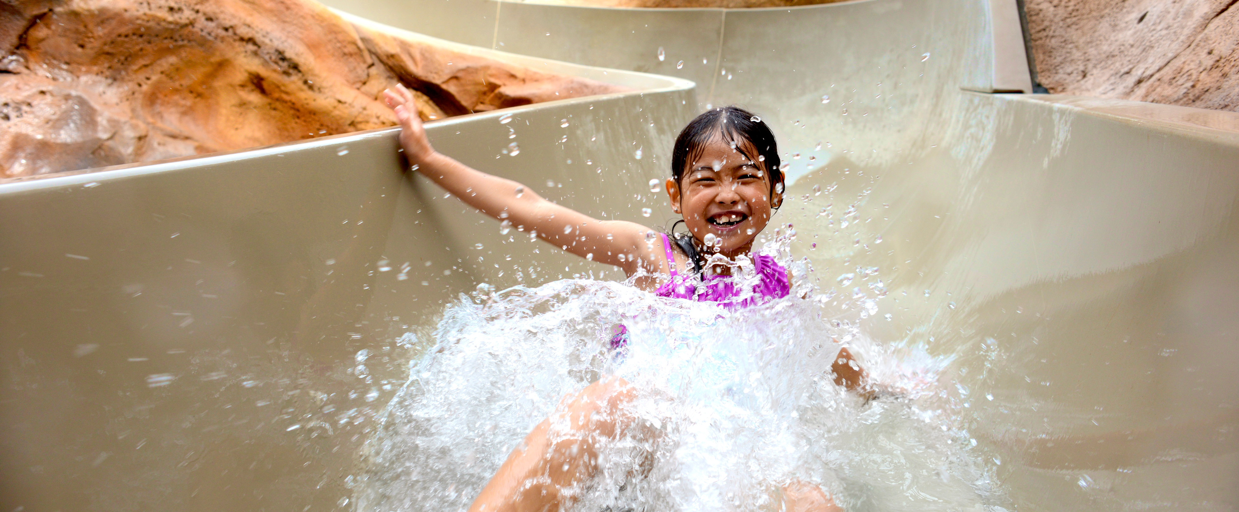 A young girl grins broadly as she splashes to the bottom of a water slide