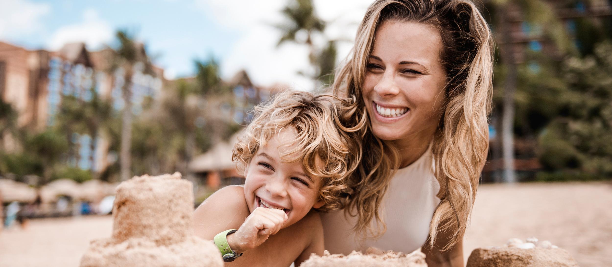 コオリナ・ビーチで砂のお城を作る笑顔のママと男の子