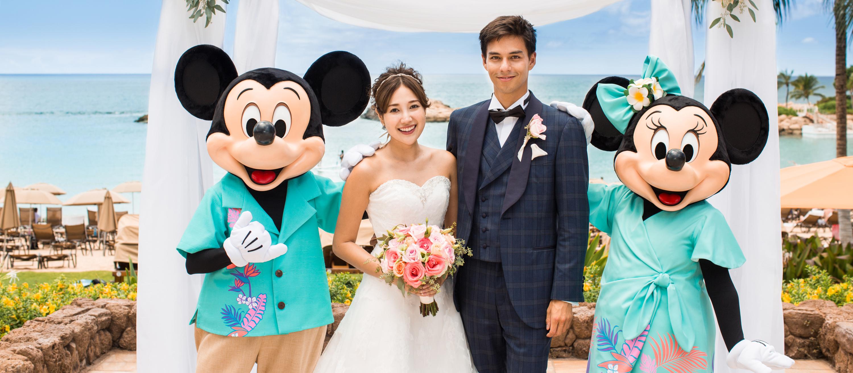 青い海を背景にしてアマアマ・パティオでキャラクターに祝福されながら挙式を上げるカップル