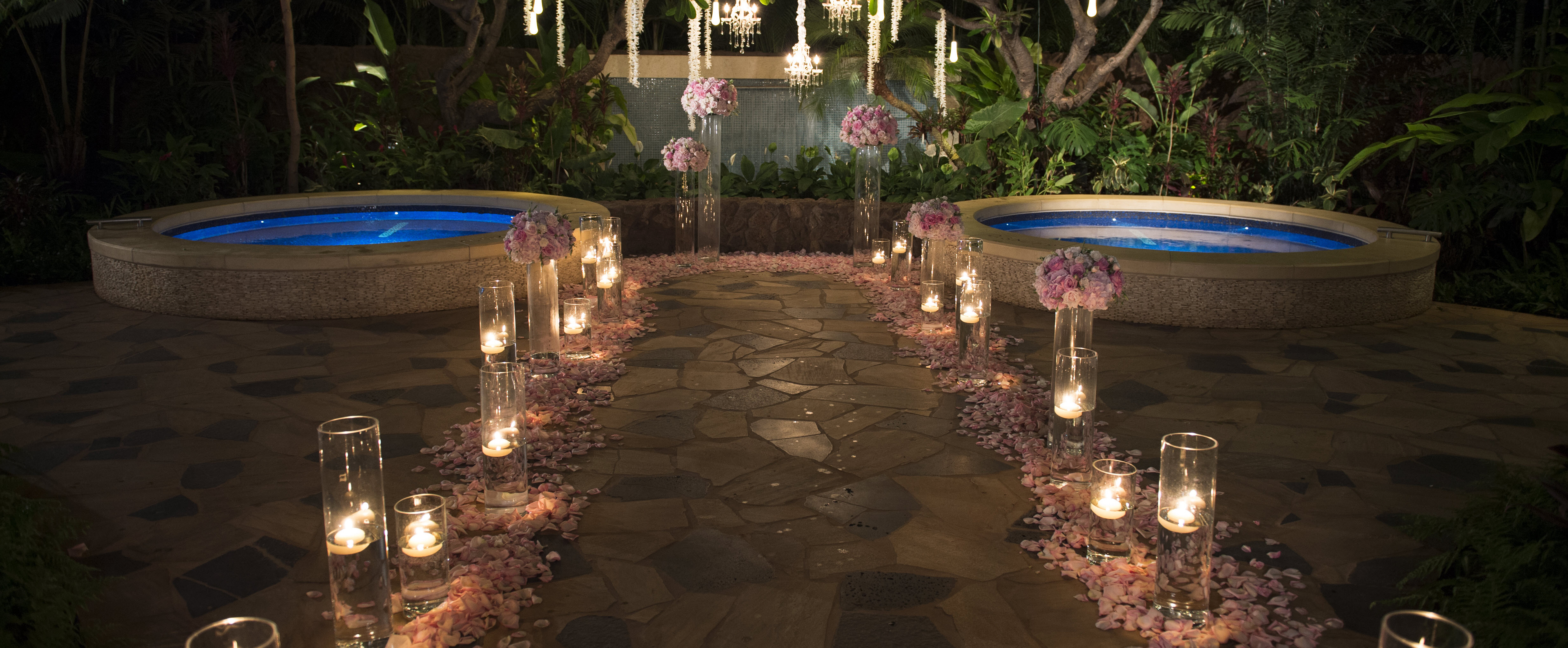 An evening garden setting with 2 round pools and an aisle lined with rose petals, bouquets and floating candles