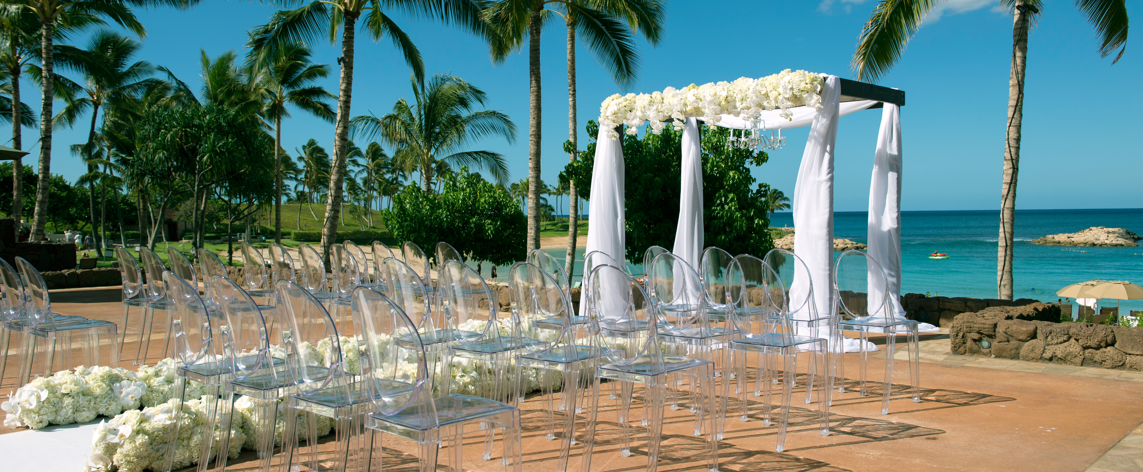 Weddings at disney parks and resorts - Rows Of Transparent Chairs Line An Aisle Leading To A Seaside Altar Draped In White Fabric Weddings And Celebrations