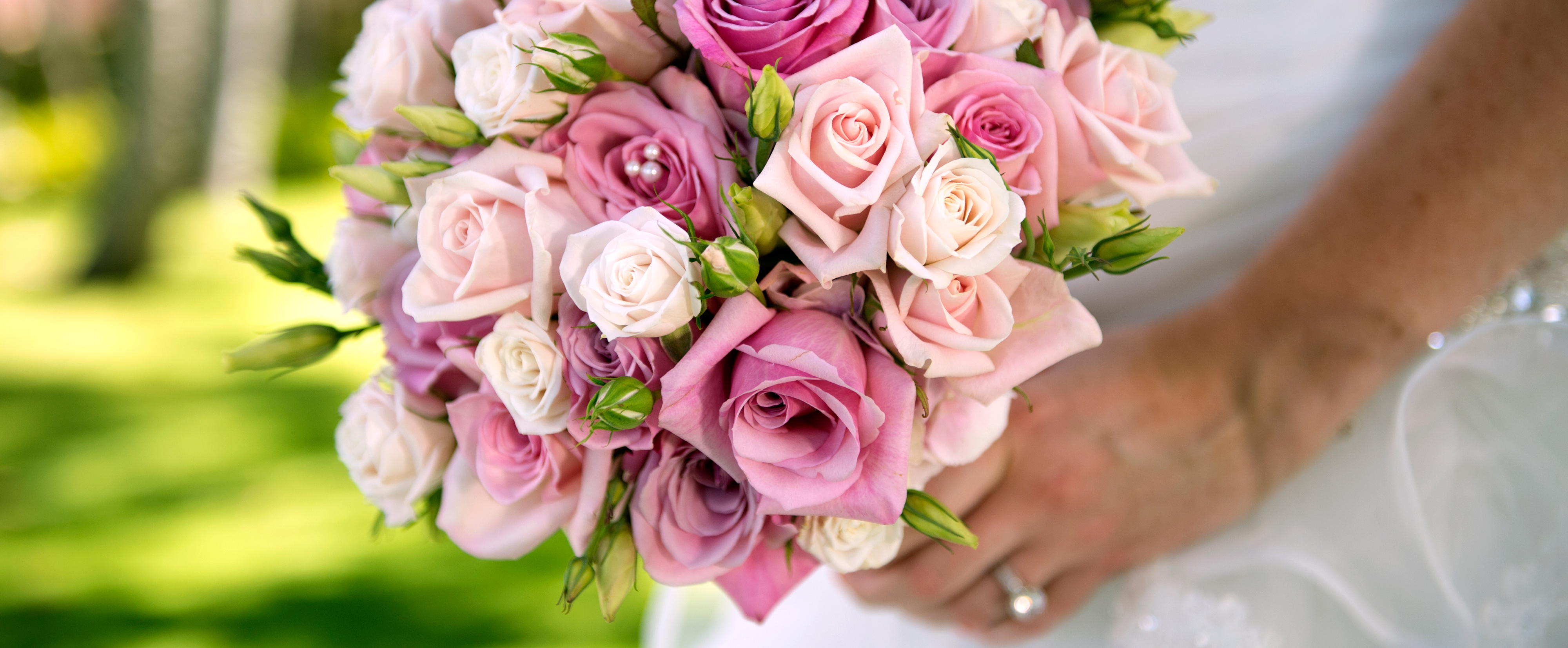 A bouquet of pale- and bright-pink roses with a pearl embellishment in a bride's hands